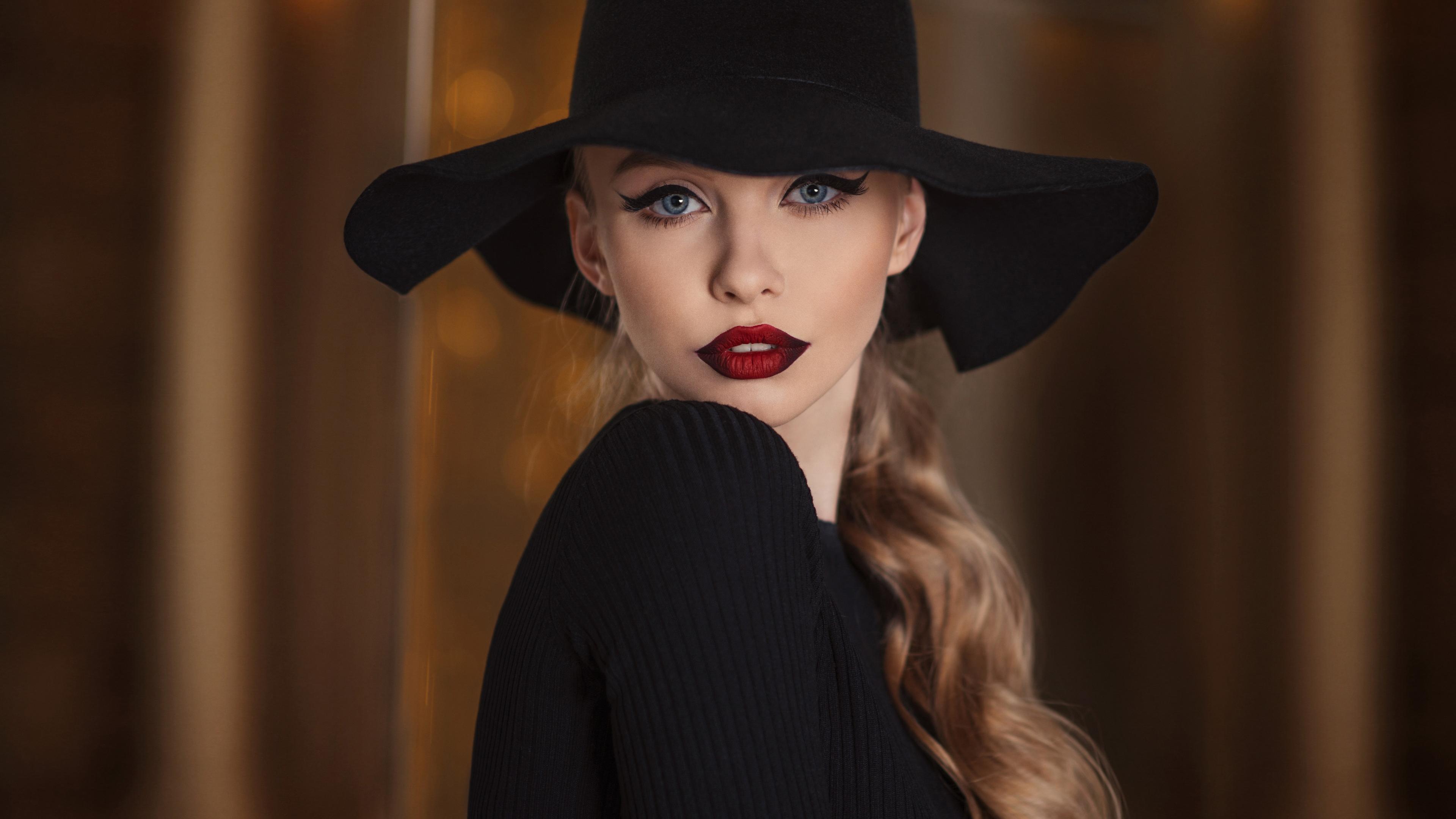 Светловолосая девушка в черной шляпе