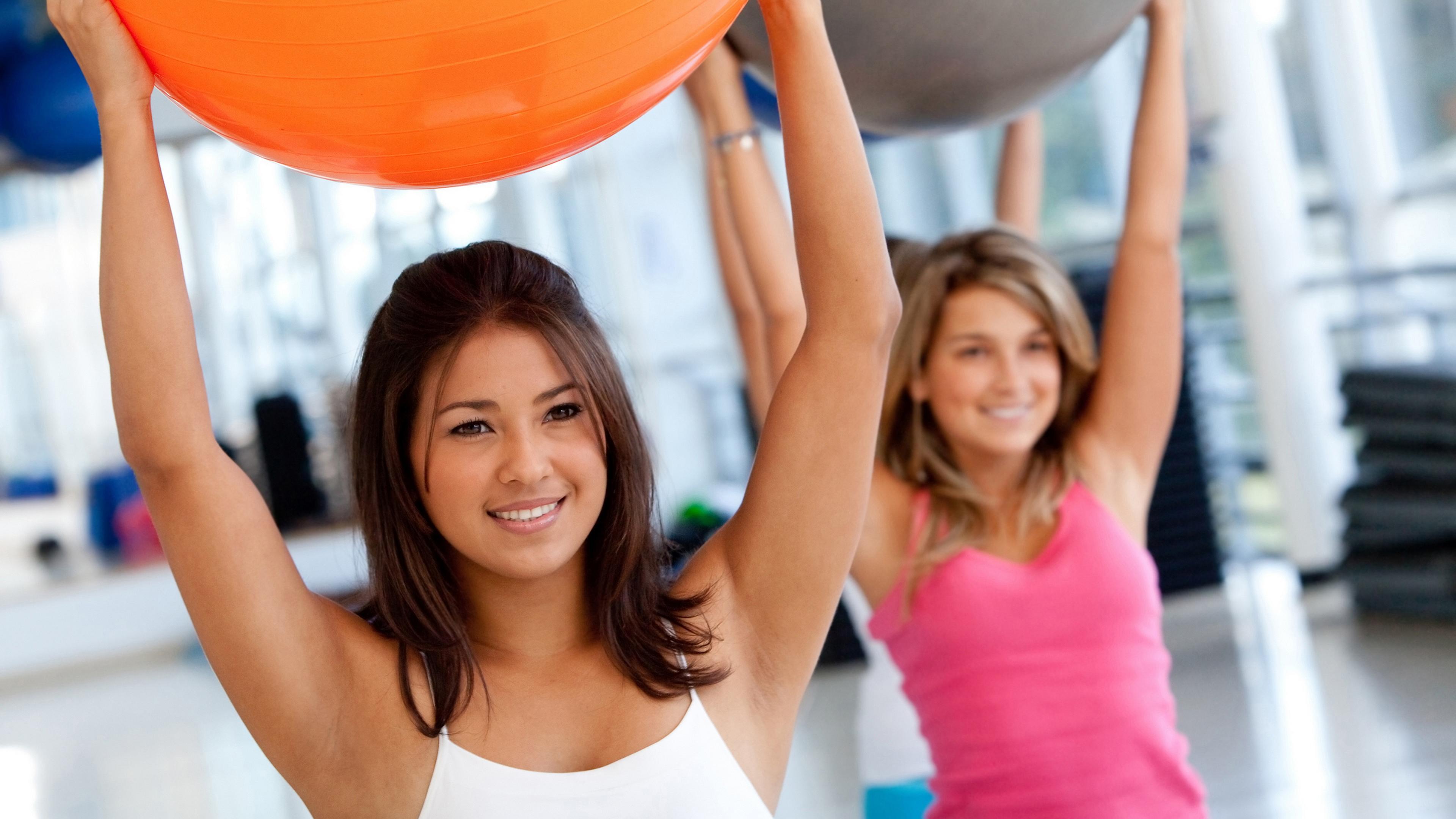 Молодые девушки с шарами в спортзале