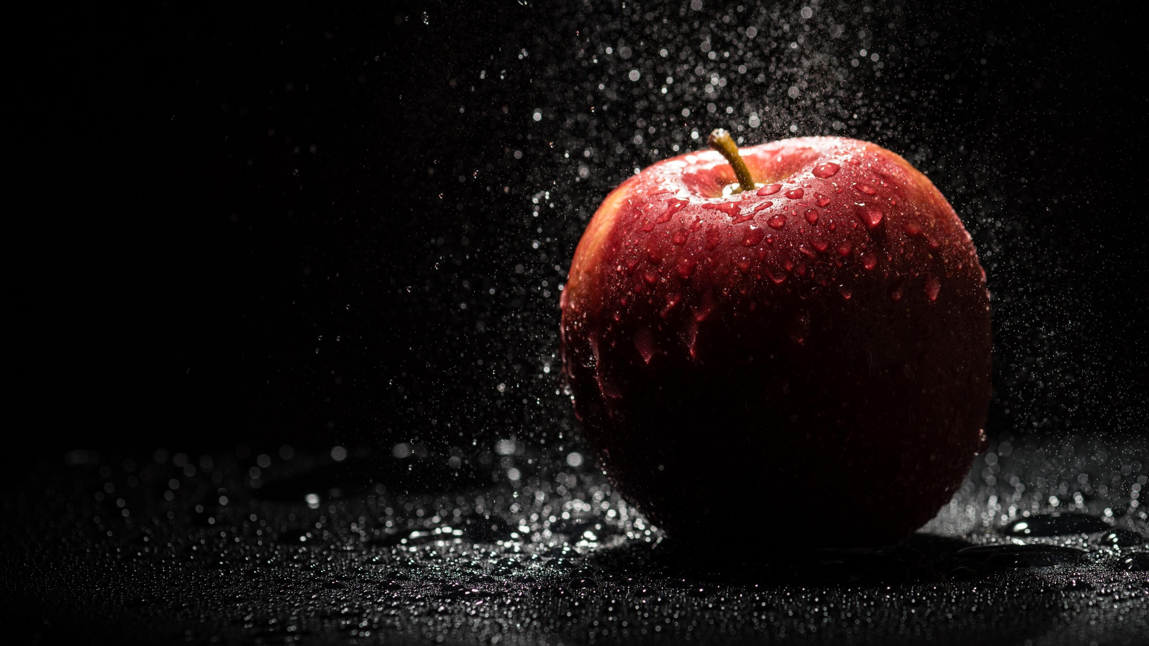 Красное яблоко на земле в каплях дождя