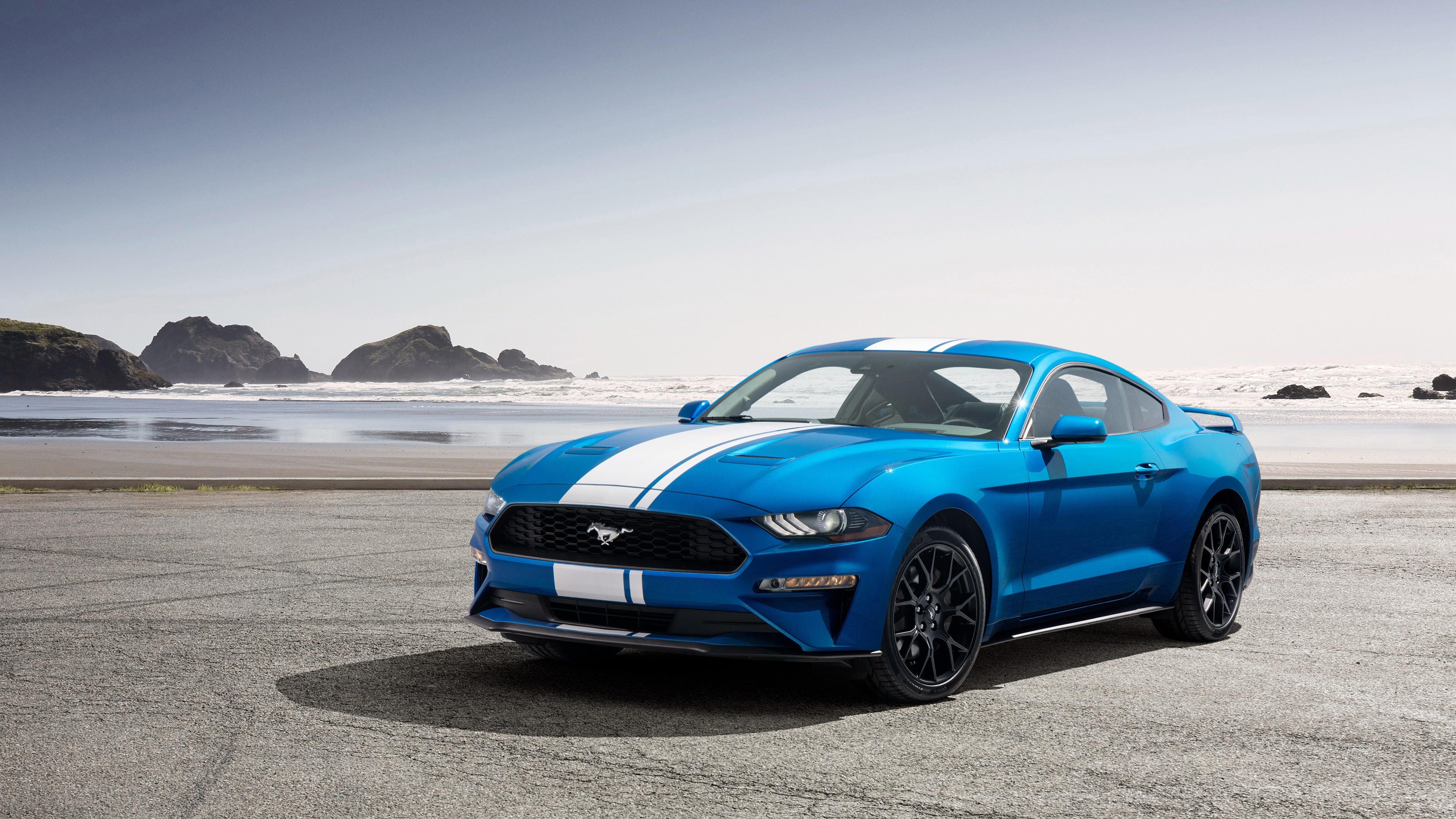 Синий спортивный автомобиль с белой полосой на фоне горных вершин и морских волн