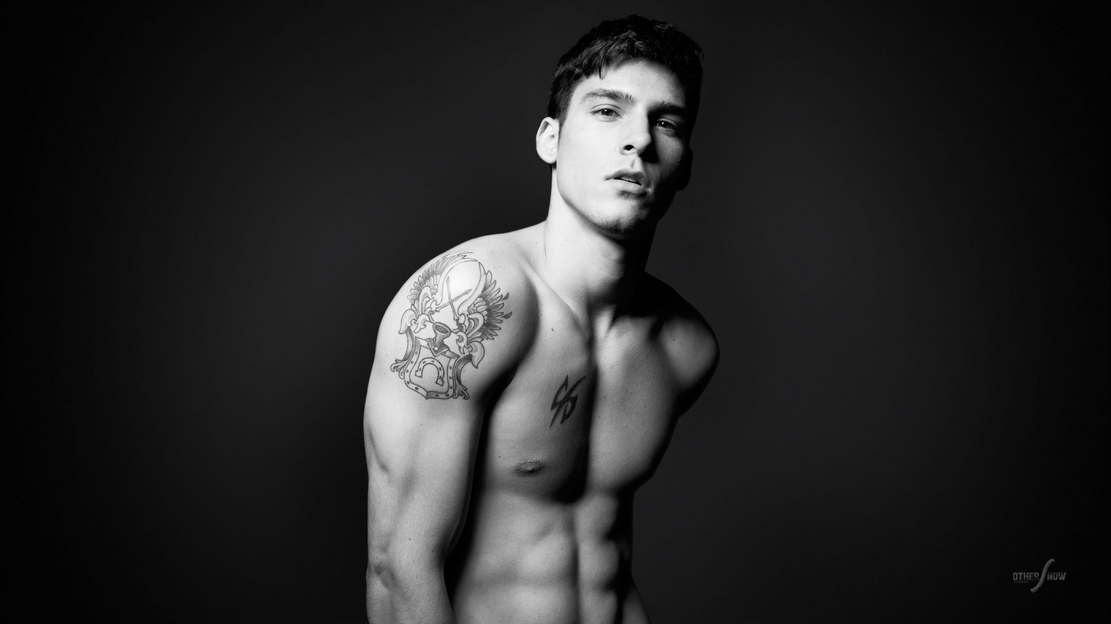 Молодой человек спортивного телосложения с татуировкой на плече