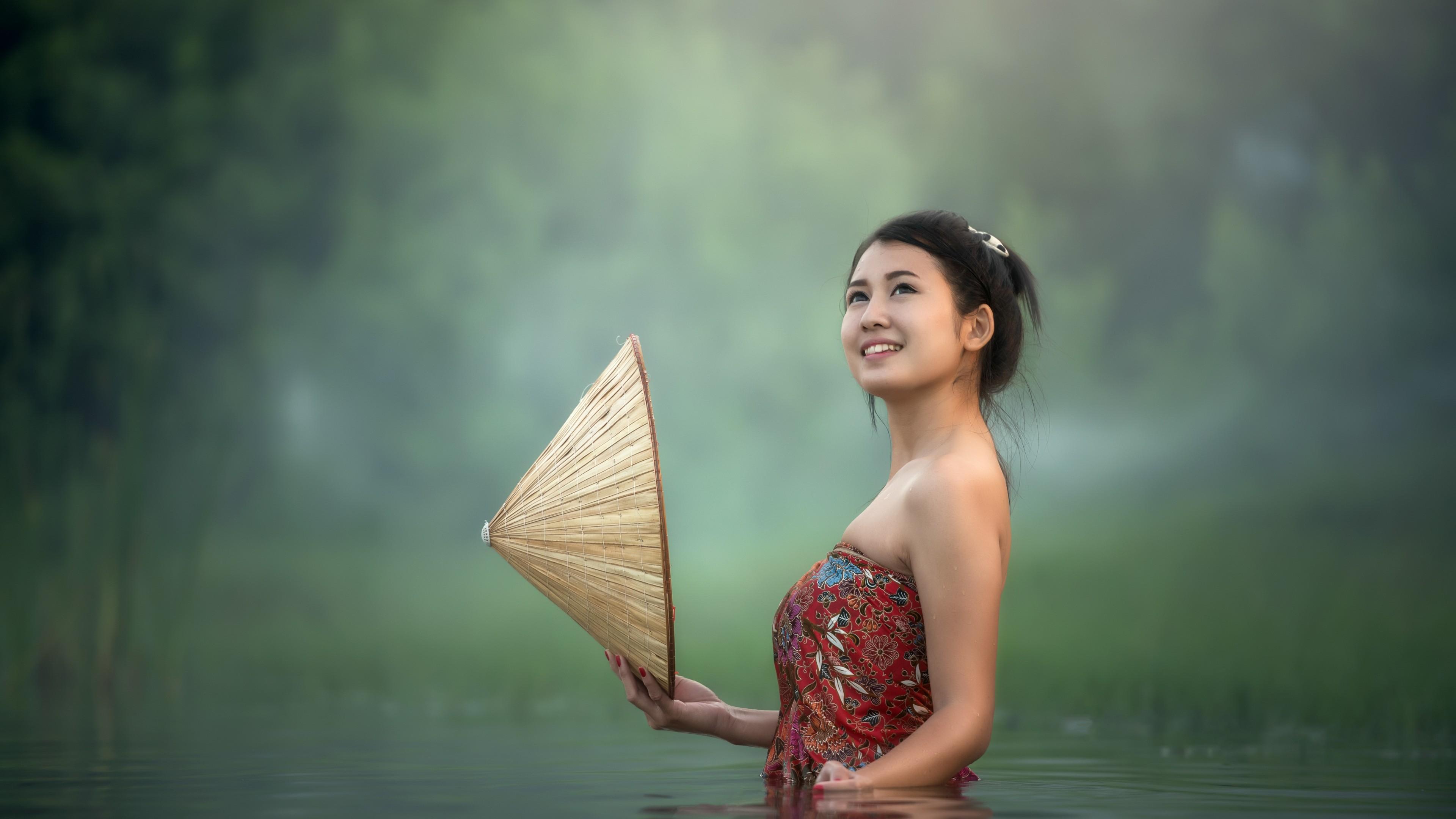 Девушка-азиатка с конической шляпой в руке принимает утренние процедуры в пруду