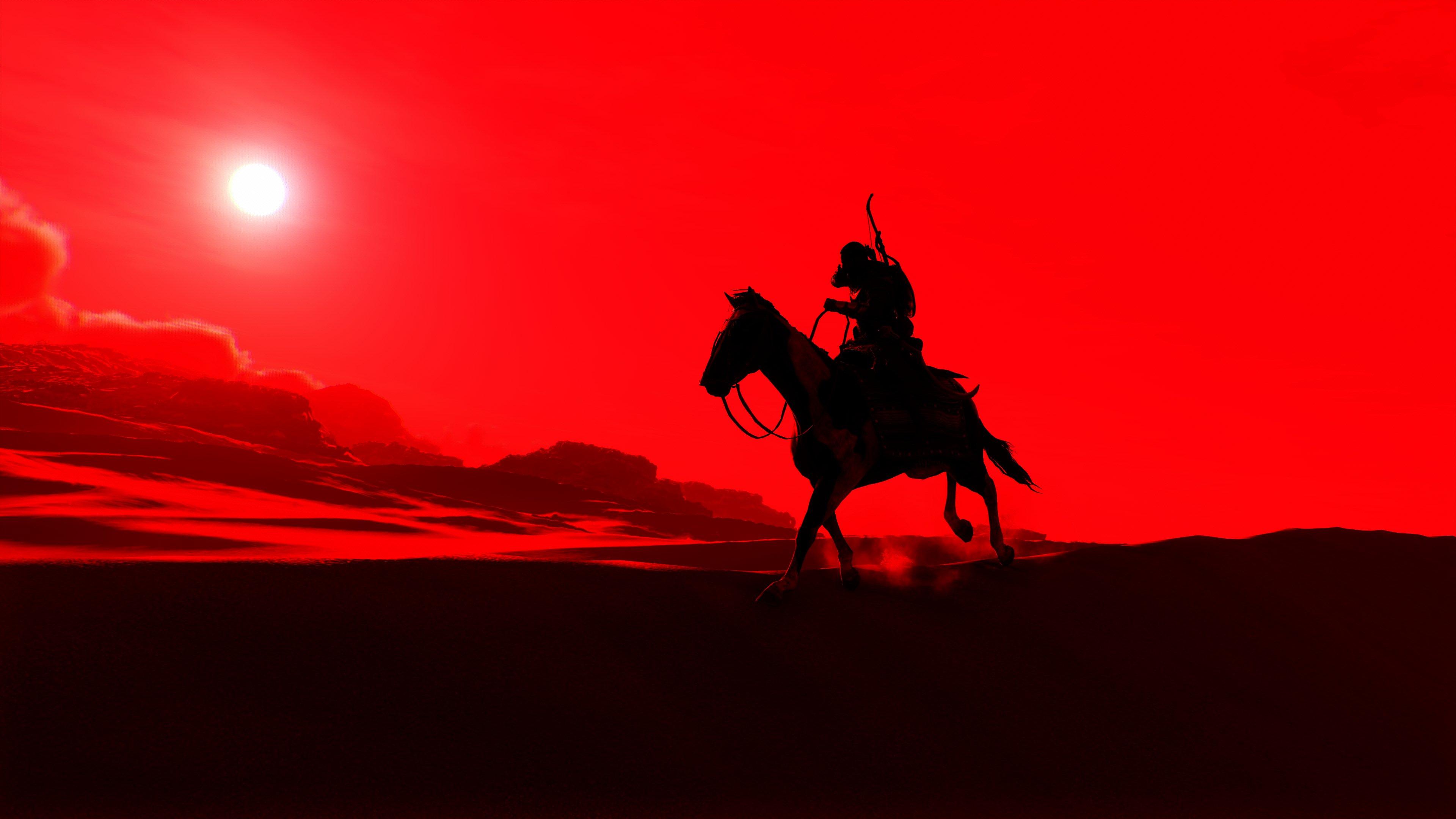 Силуэт лошади с наездником на фоне красного заката в пустыне