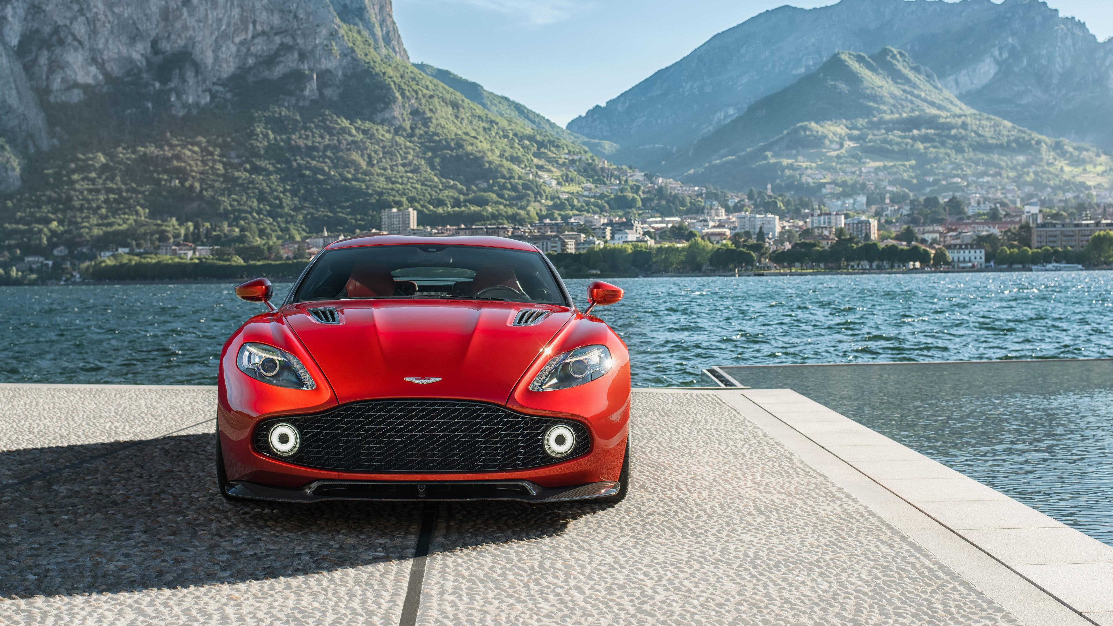 Красный спортивный автомобиль на фоне горных вершин и сине-изумрудных волн моря