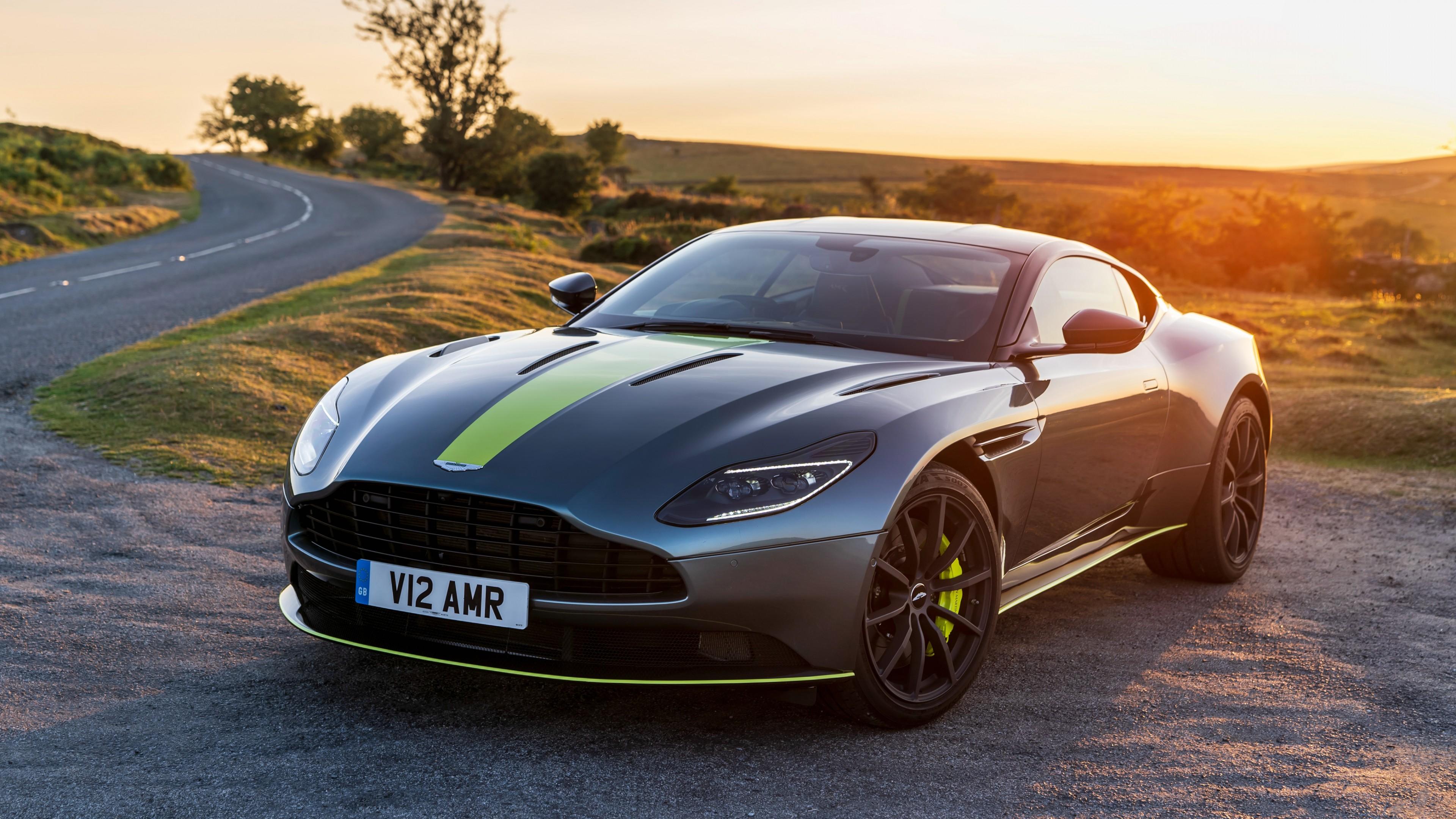 Престижный спортивный автомобиль серебристо-серого цвета с зеленой полосой в золотых лучах