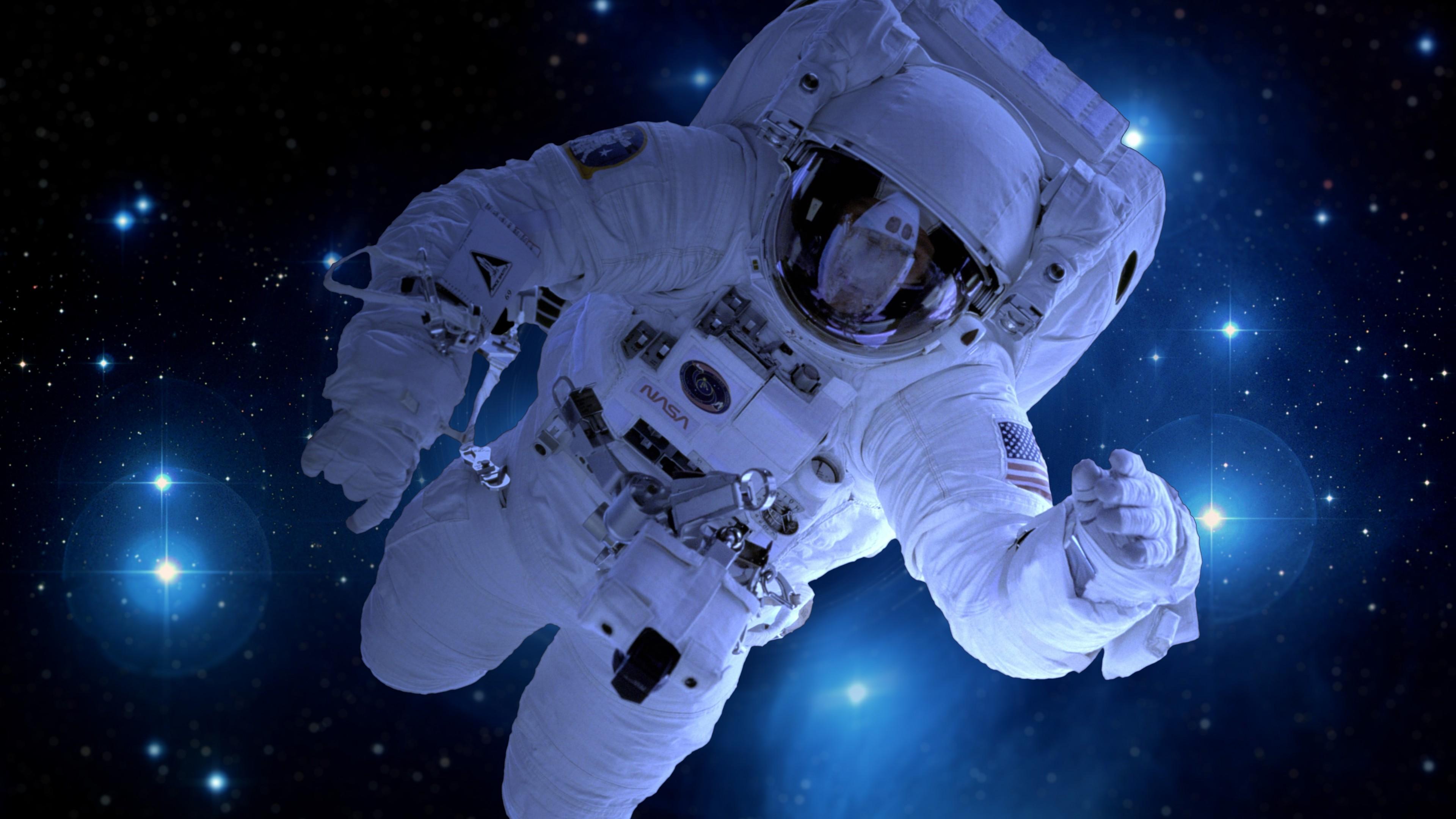 Астронавт в космическом скафандре,комбинезоне  в открытом космосе среди сверкающих звезд