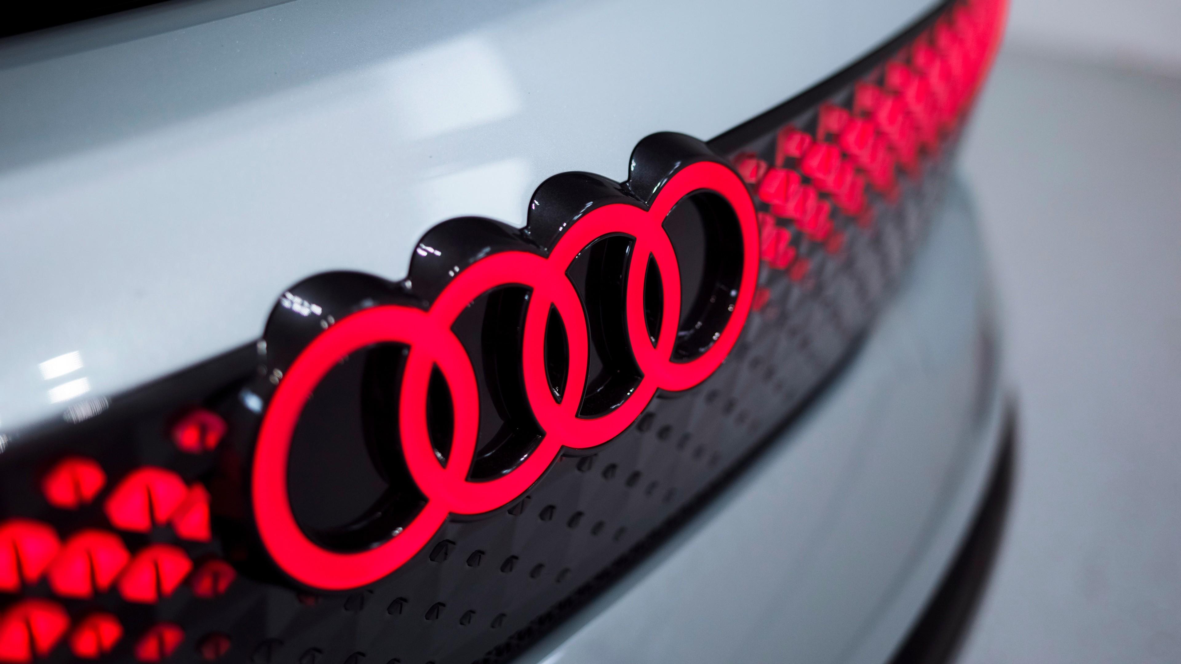 Ярко-красный логотип белого блестящего автомобиля Ауди