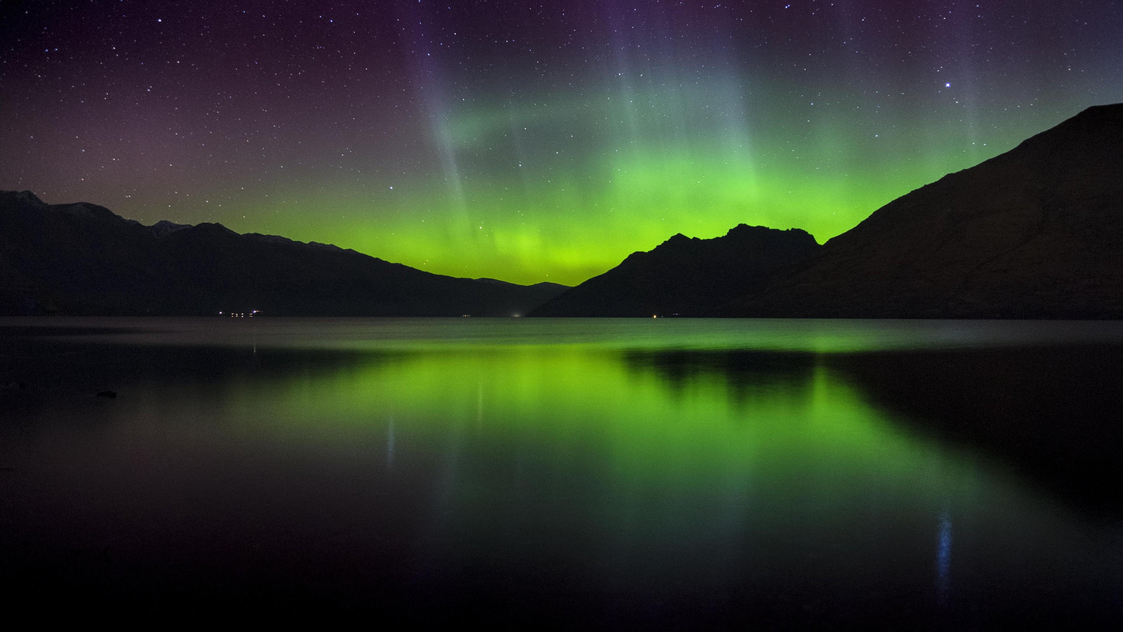 Ночное северное сияние со звездным дождем в горных вершинах и изумрудном озере