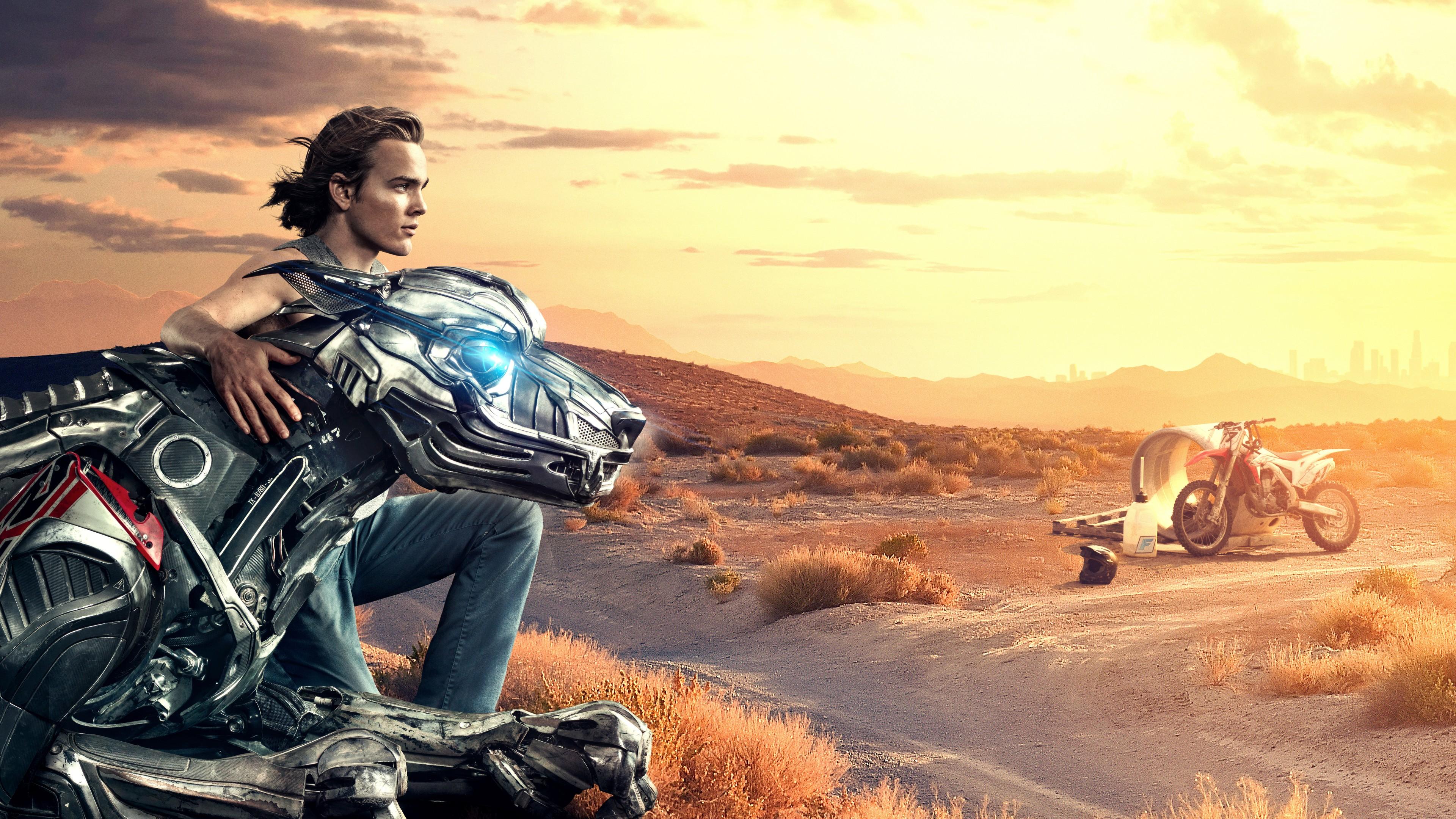 Молодой человек в обнимку с роботом в горах в отблесках солнца