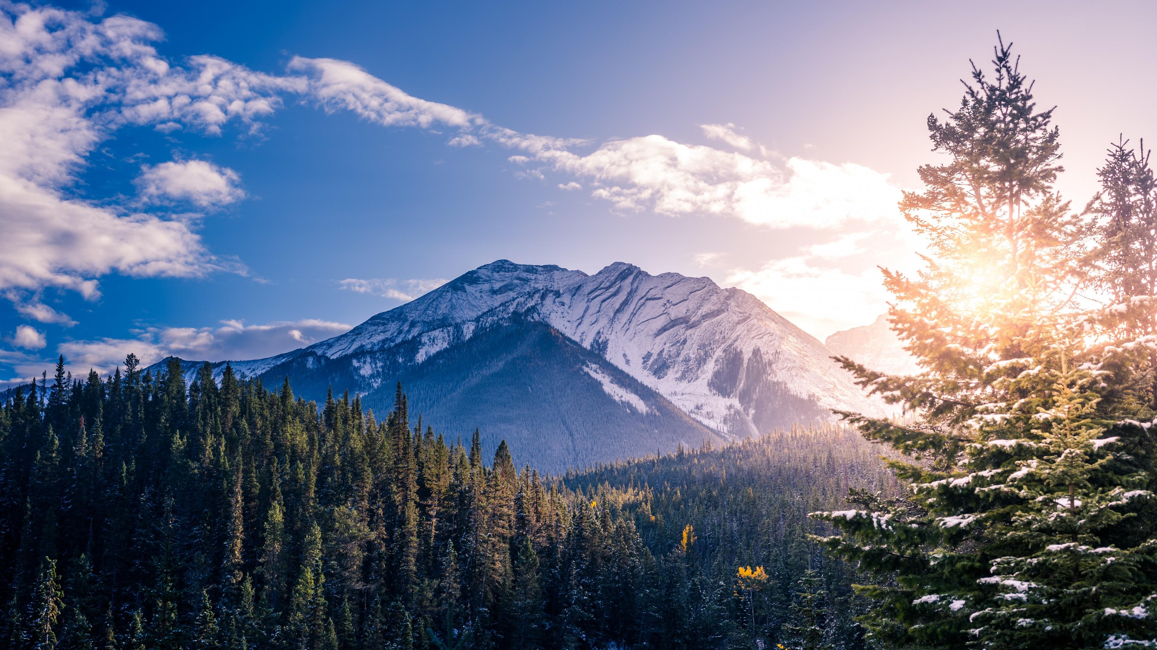 Горные снежные вершины под золотыми облаками заходящего солнца