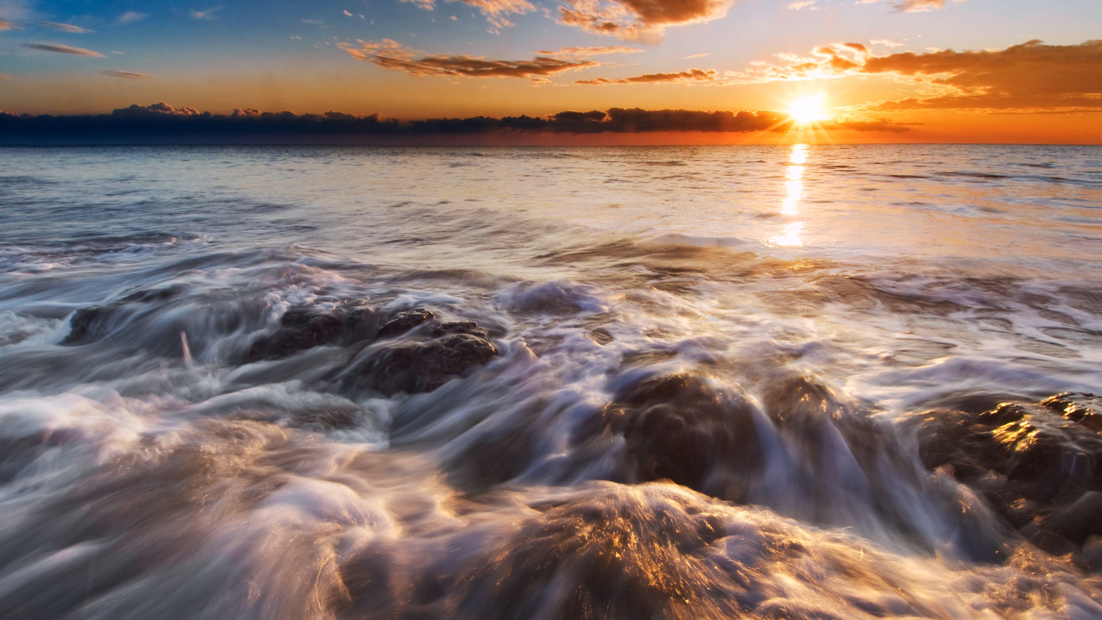 Оранжево-рыжий закат огненного солнца на бушующем морском прибое