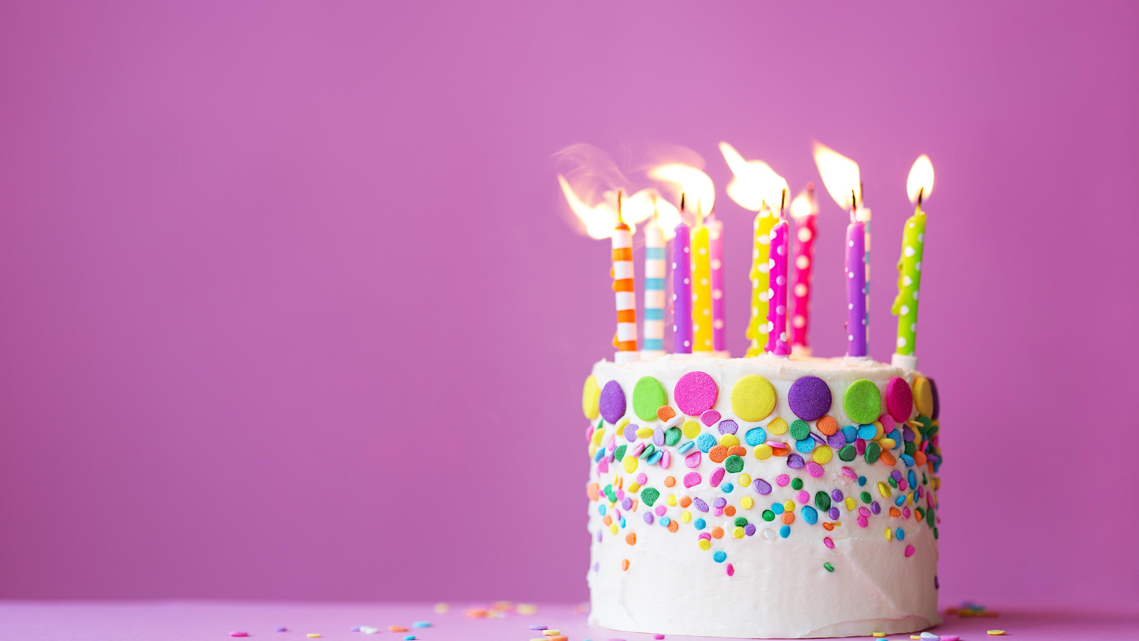 Праздничный торт с разноцветными пылающими пламенем свечей на сиреневом фоне