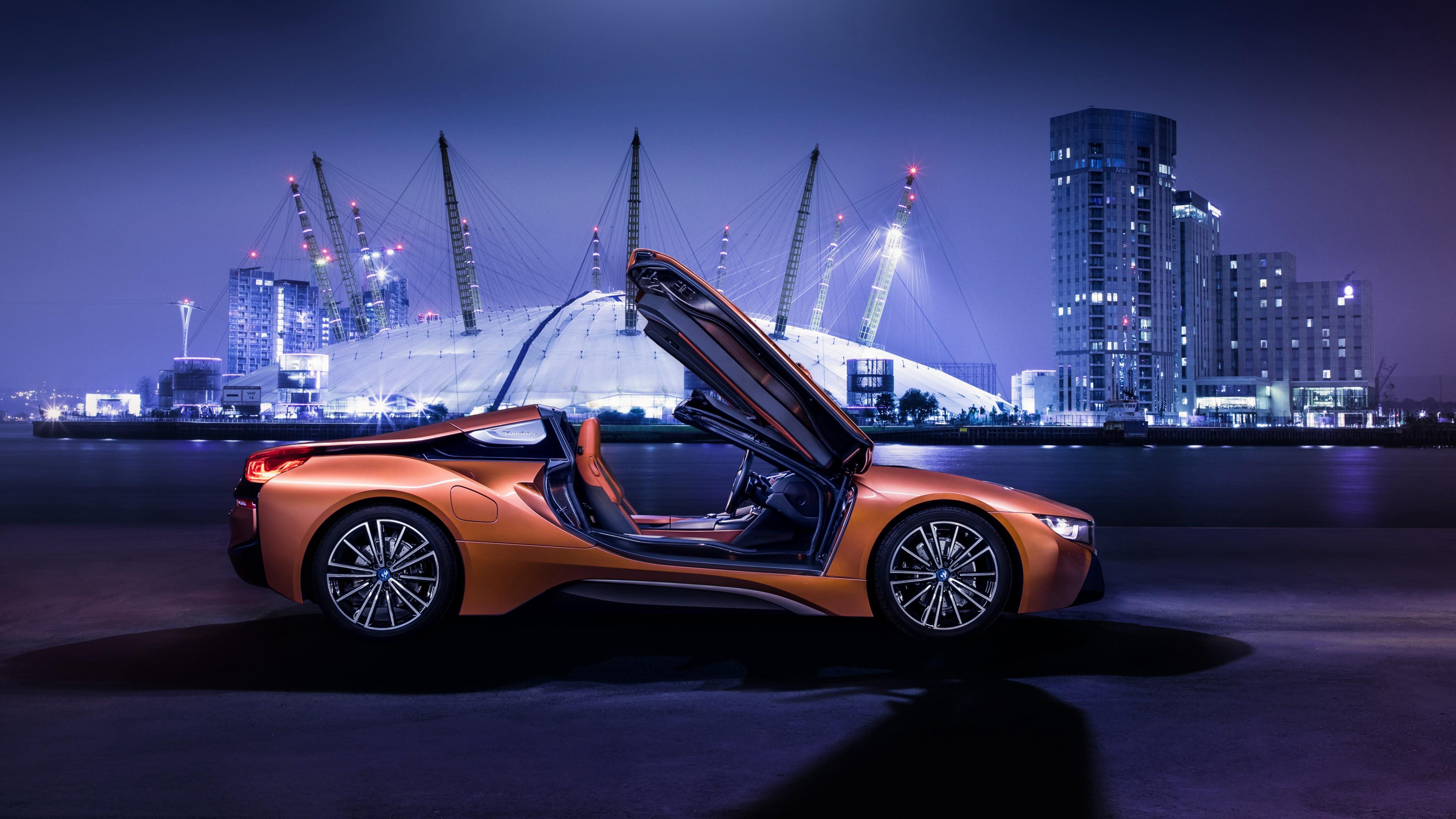Спортивный оранжевый автомобиль с открытыми дверями в ночном городе