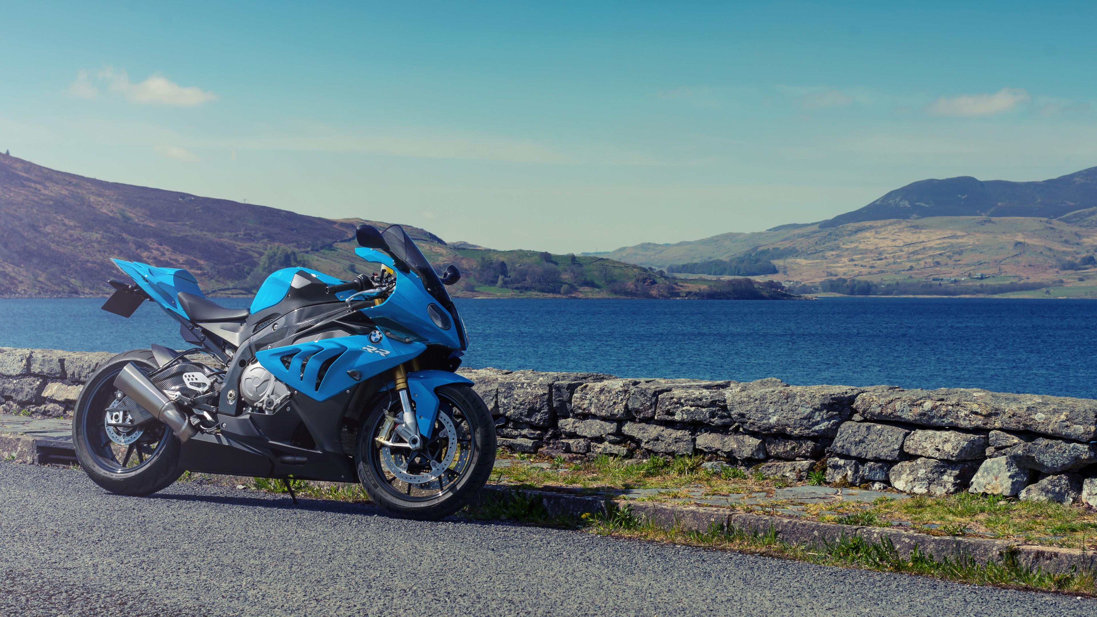 Спортивный голубой мотоцикл на фоне зеленых холмов и синего озера
