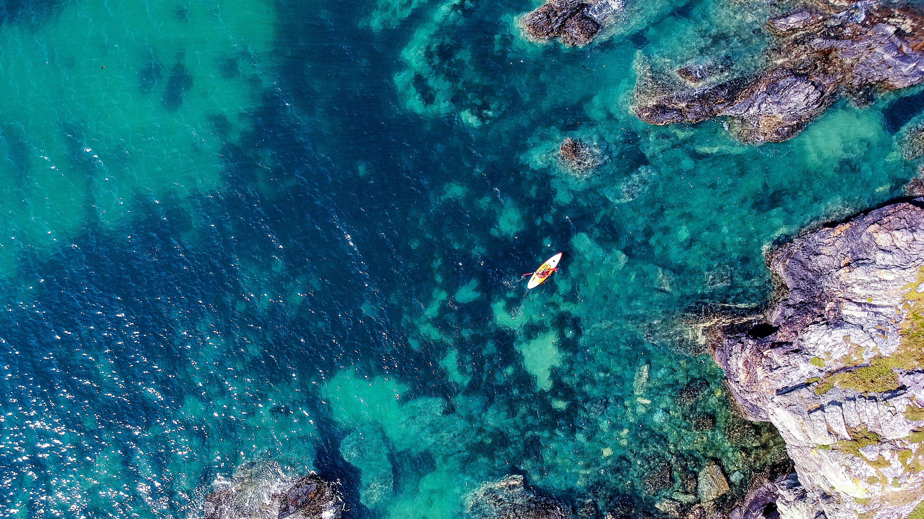 Аэрофотосъемка изумрудно-синего моря с серебристыми брызгами и горами