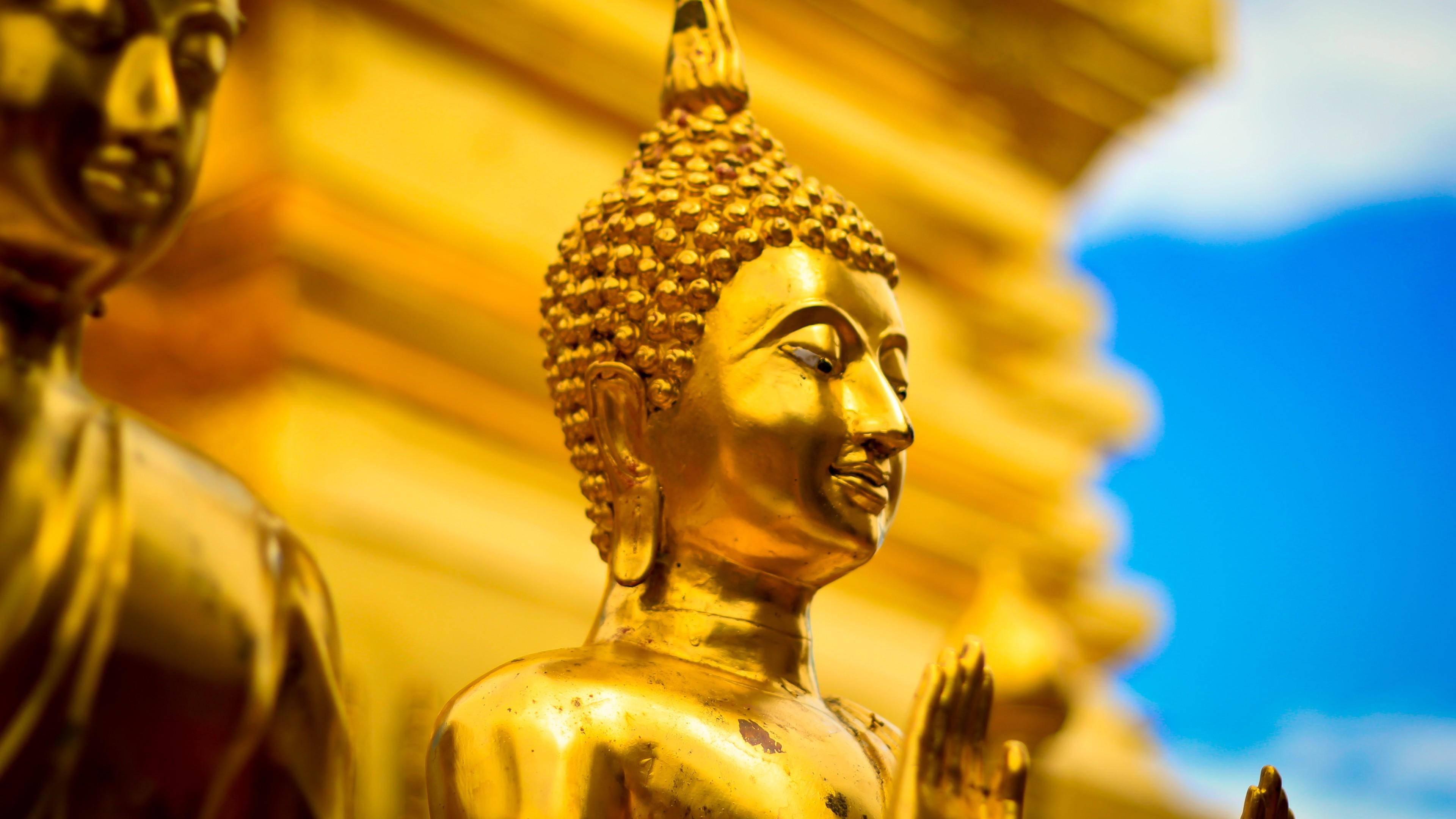 Золотая статуя с закрытыми глазами и ладонями в лучах солнца голубого неба