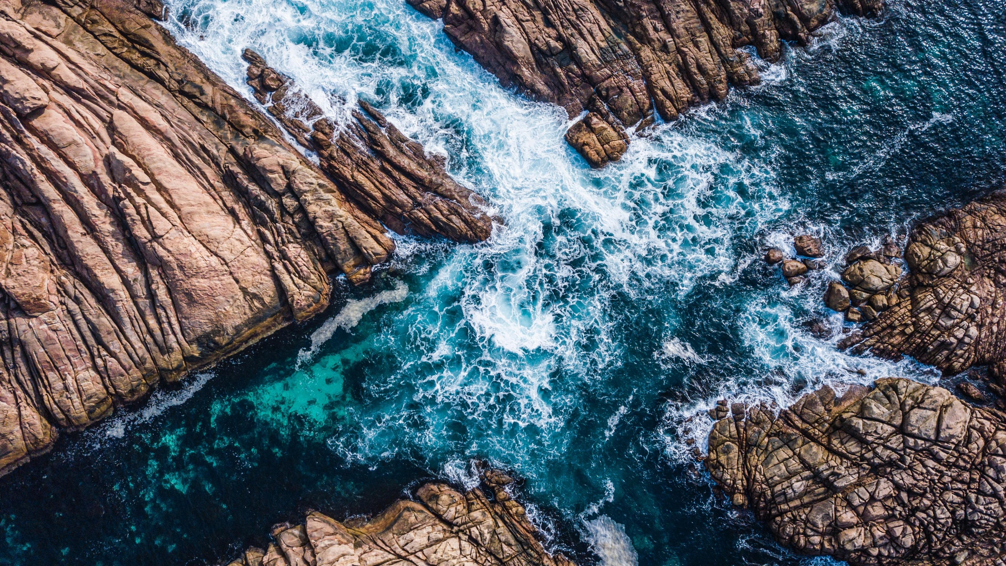 Изумрудно-синее море с белоснежной пеной и брызгами в окружении рельефных скал
