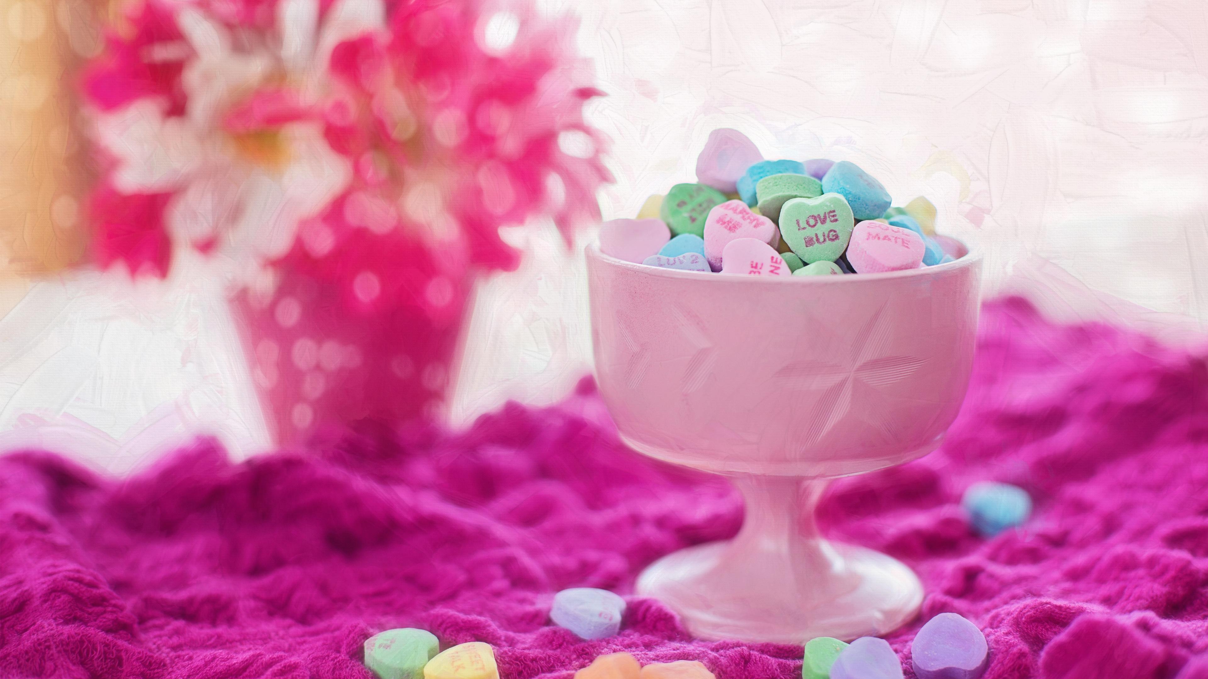 Праздничный стол с розовой вазой сладких сердечек и букетом цветов