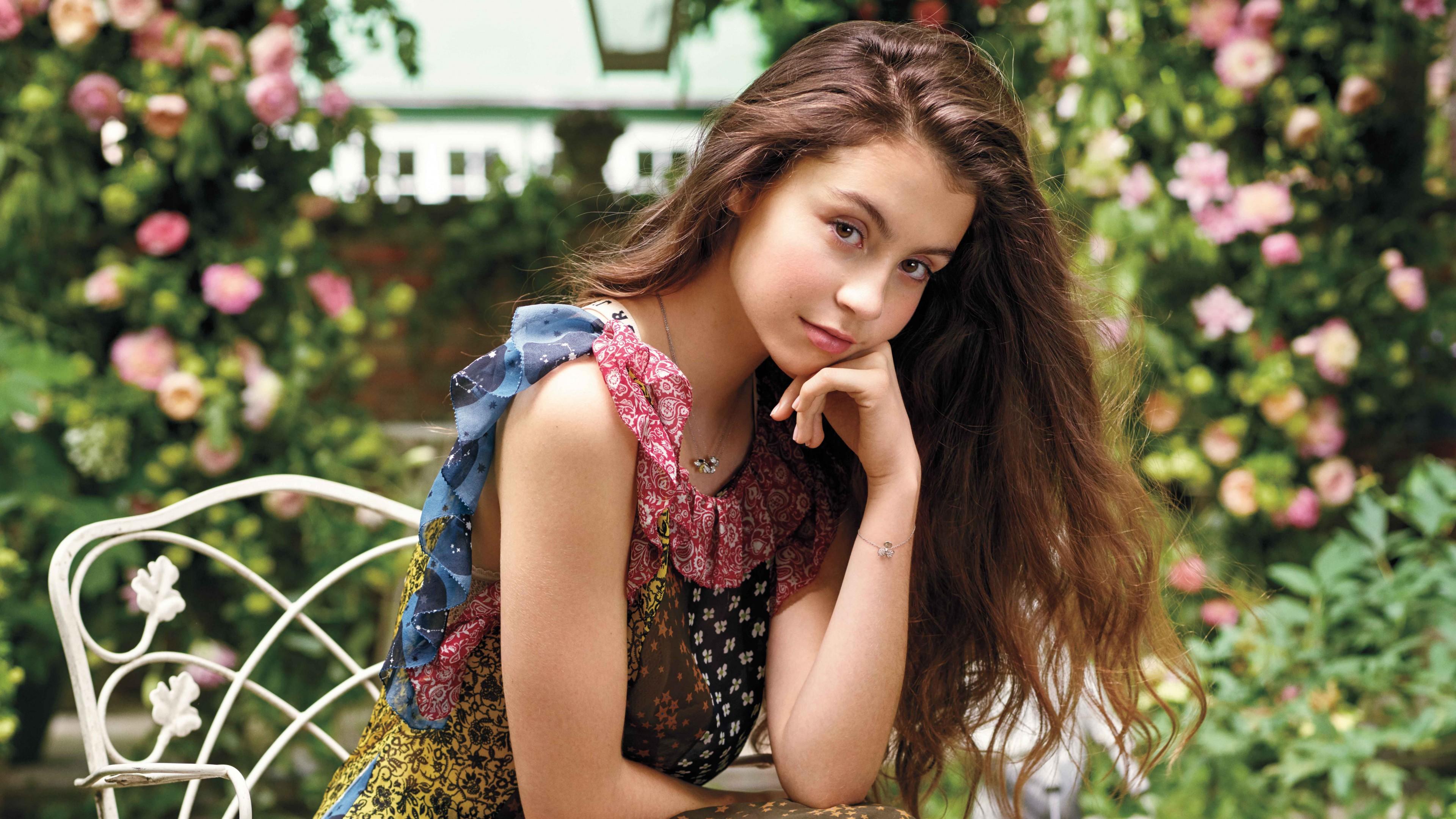 Мечтательная девушка с карими глазами в роскошном саду цветущих роз