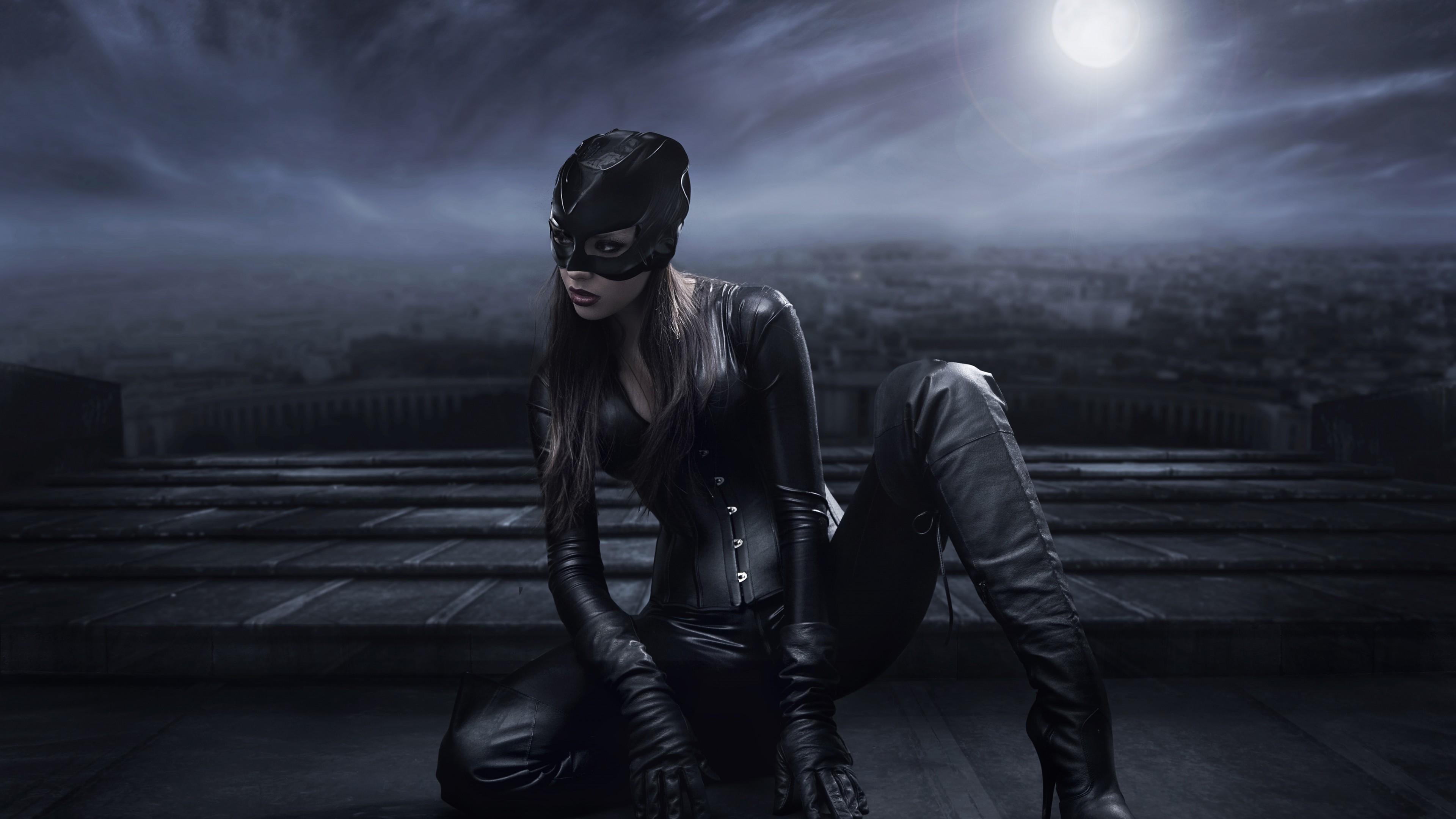 Женщина-кошка в черной кожаной маске и костюме на крыше в отблесках луны