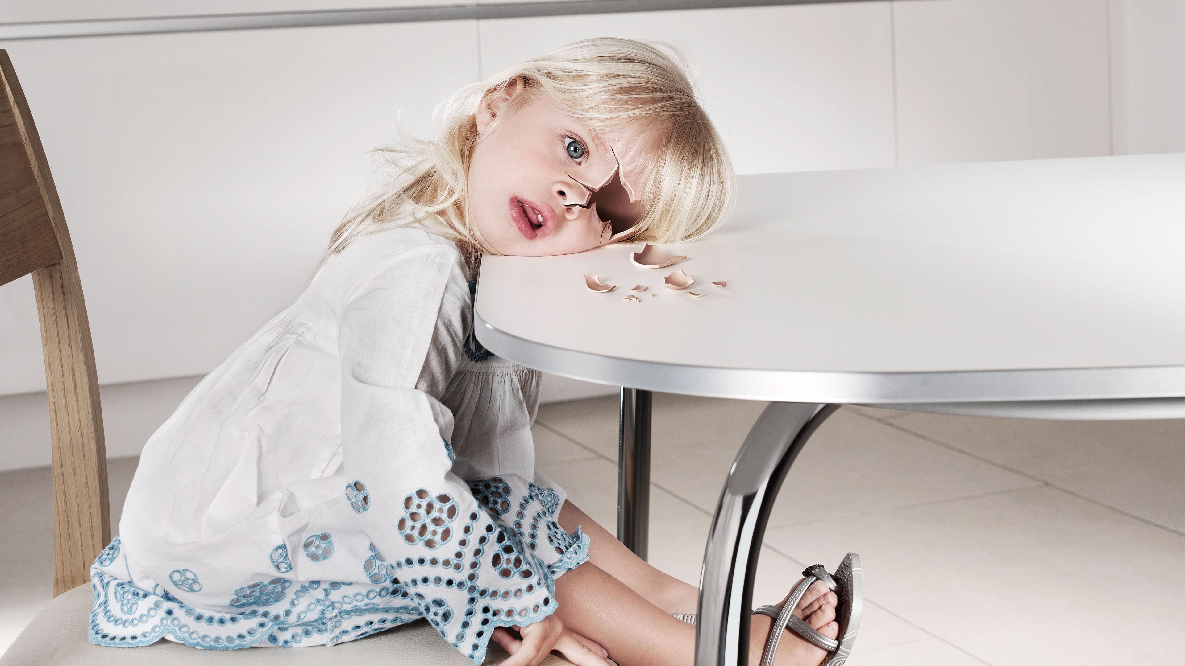 Маленькая белокурая девочка-кукла за столом