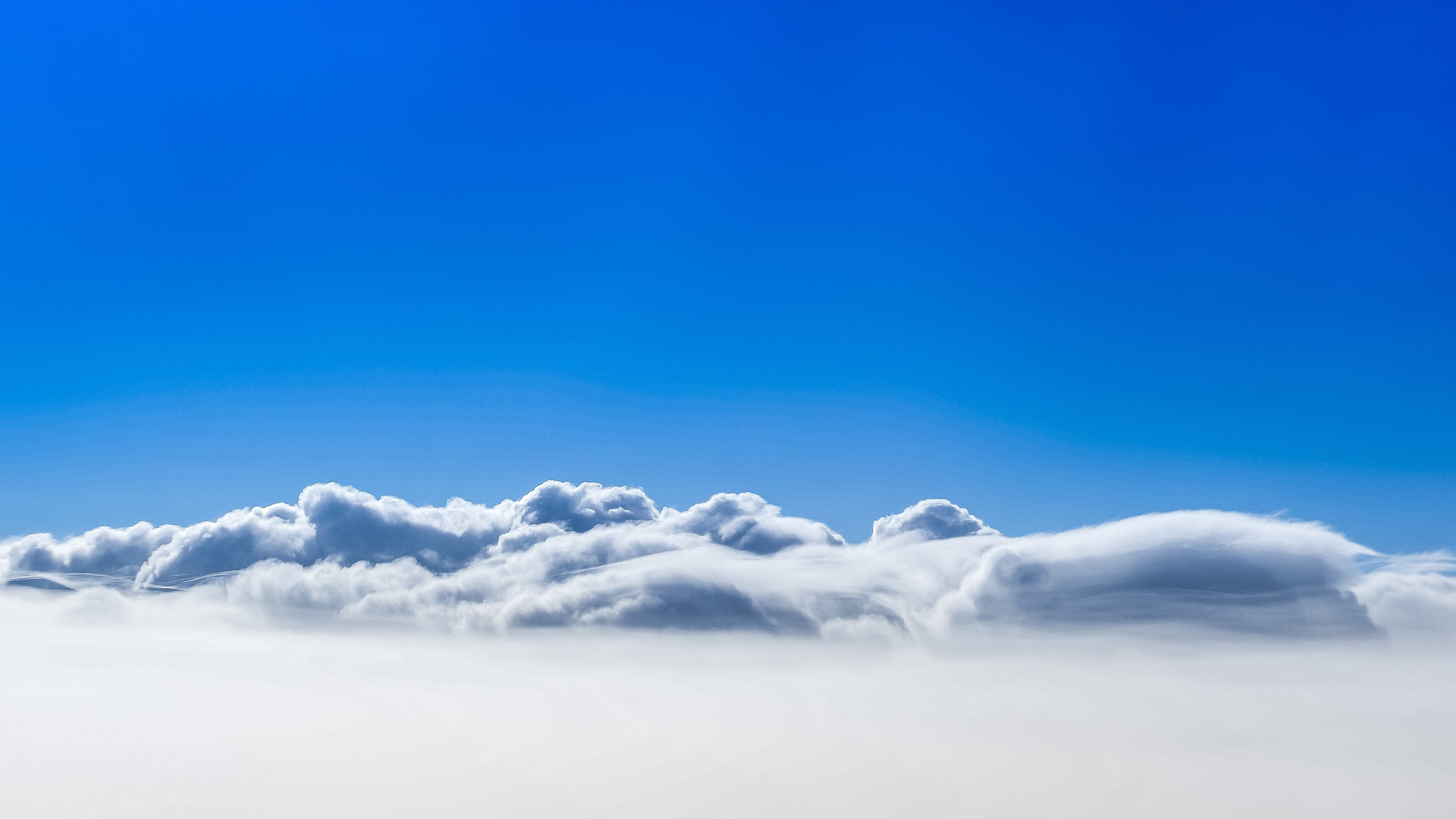 Ярко-синее небо на кучевыми серо-белыми туманными облаками
