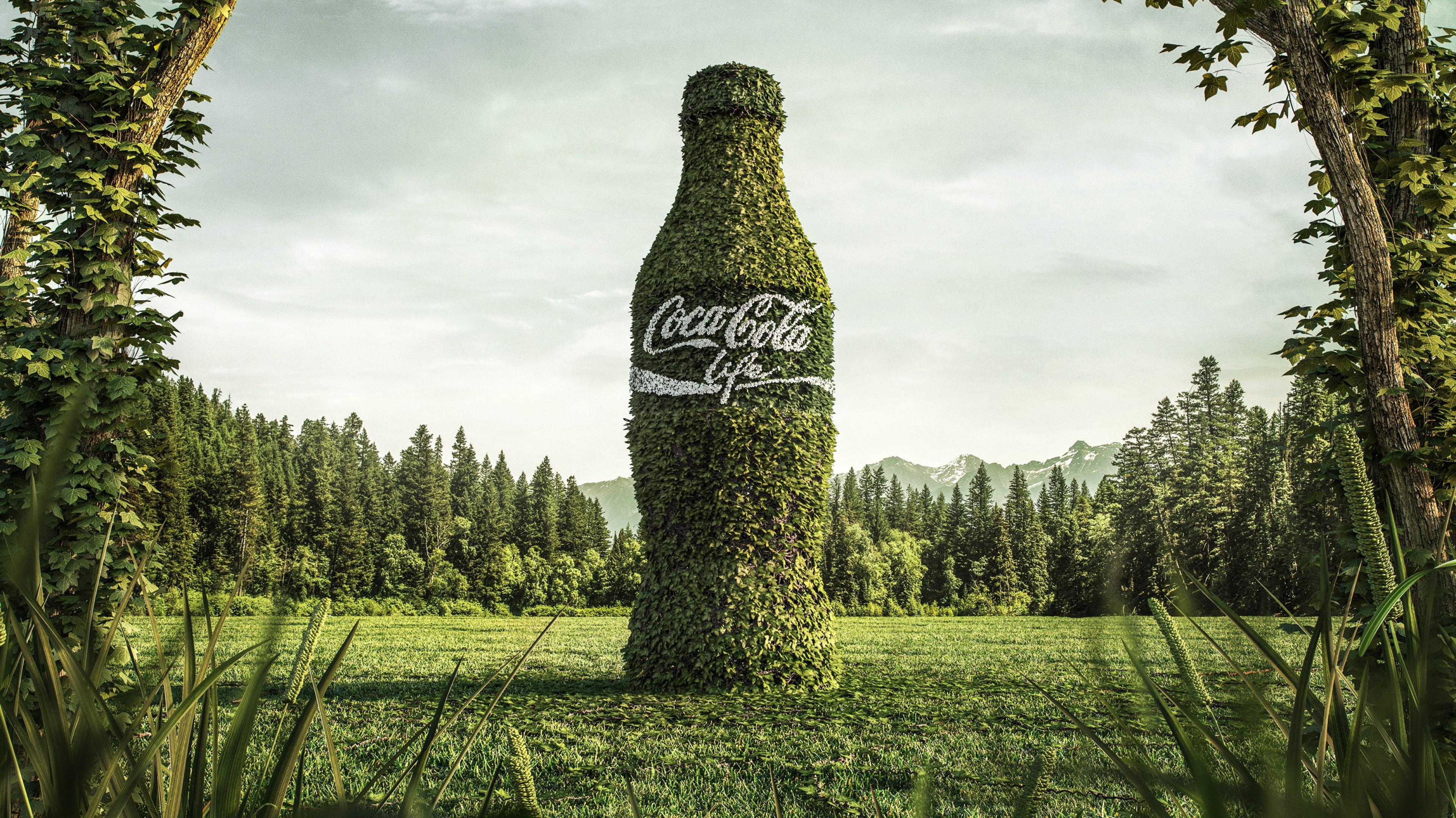 Большая бутылка,окутанная молодыми зелеными листочками на лесной поляне, с надписью Кока-кола-жизнь