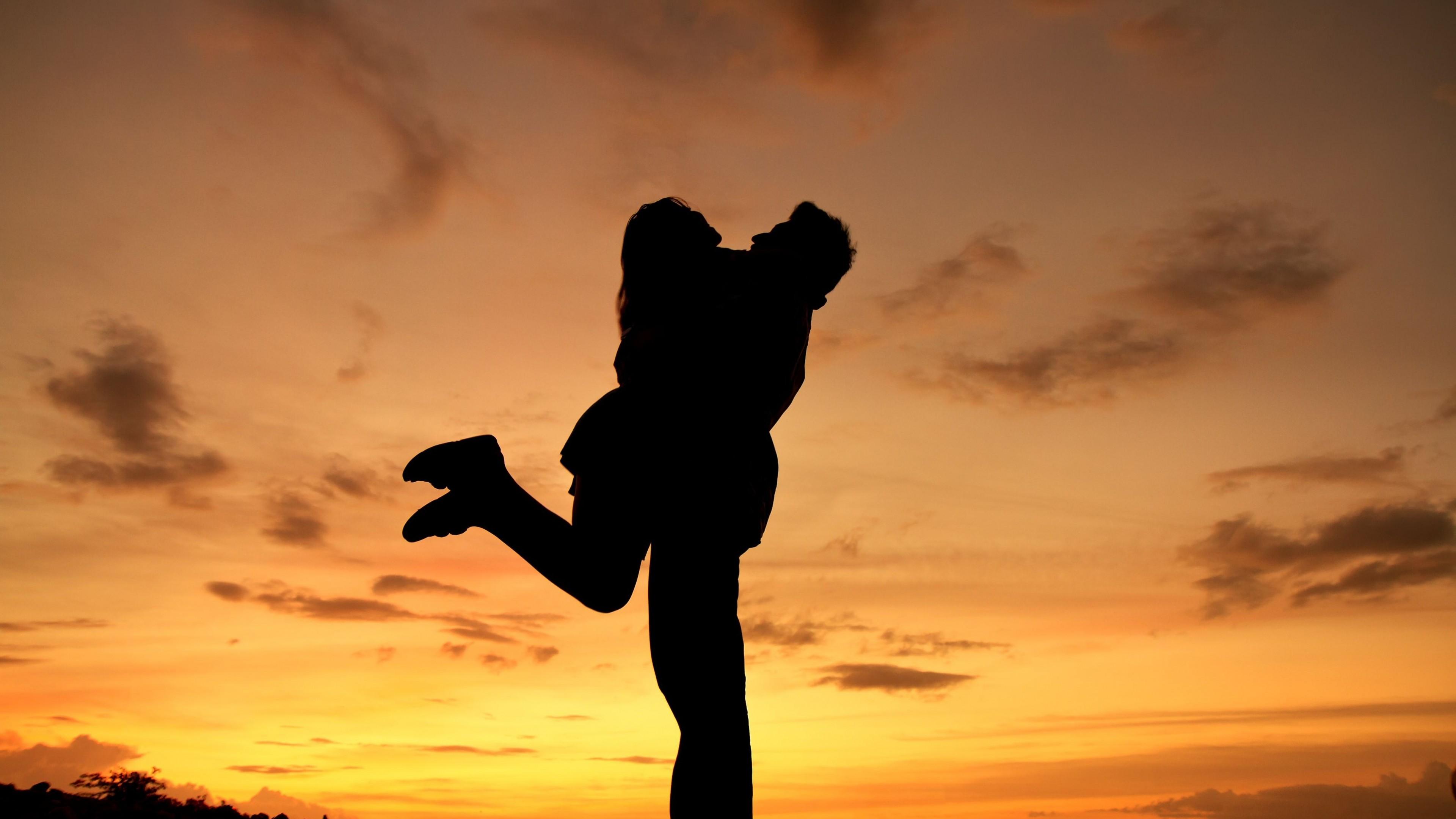 Силуэт влюбленных на фоне розово-желтого небосвода