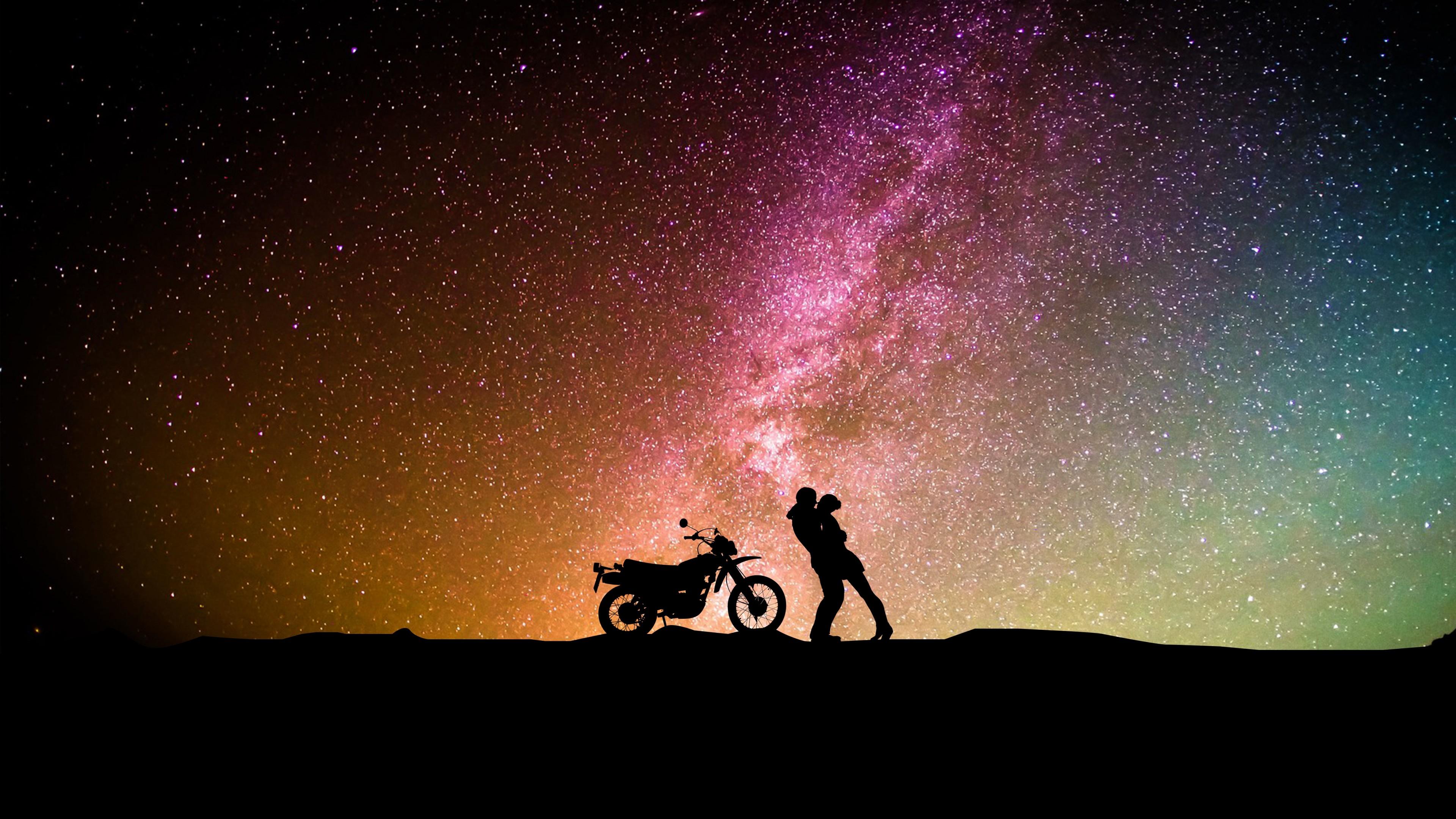 Силуэты влюбленных , мотоцикла на фоне цветных сполохов Северного сияния с ярким переливом звезд