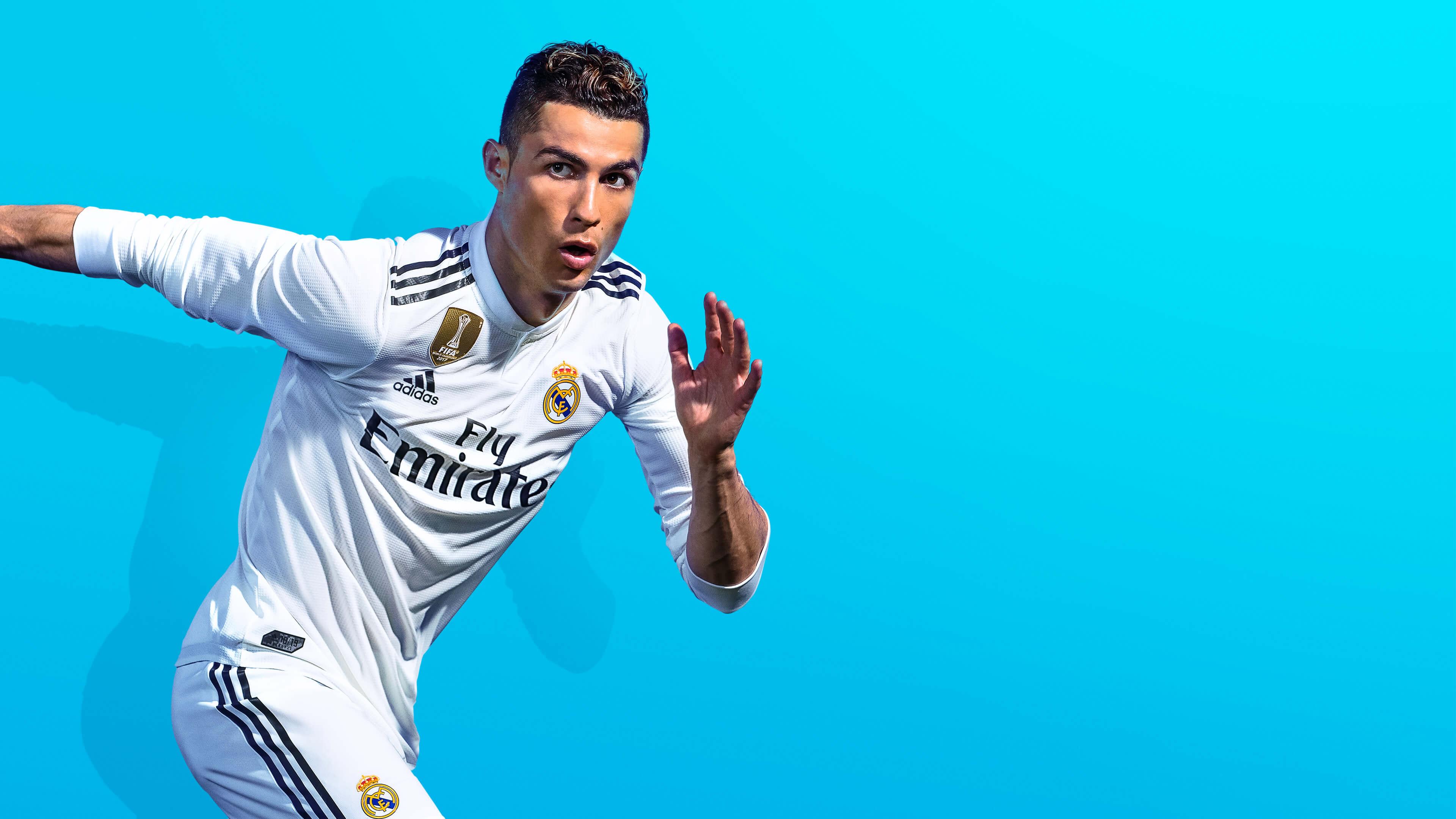 Футболист в белой экипировке с целеустремленным взглядом во время игры