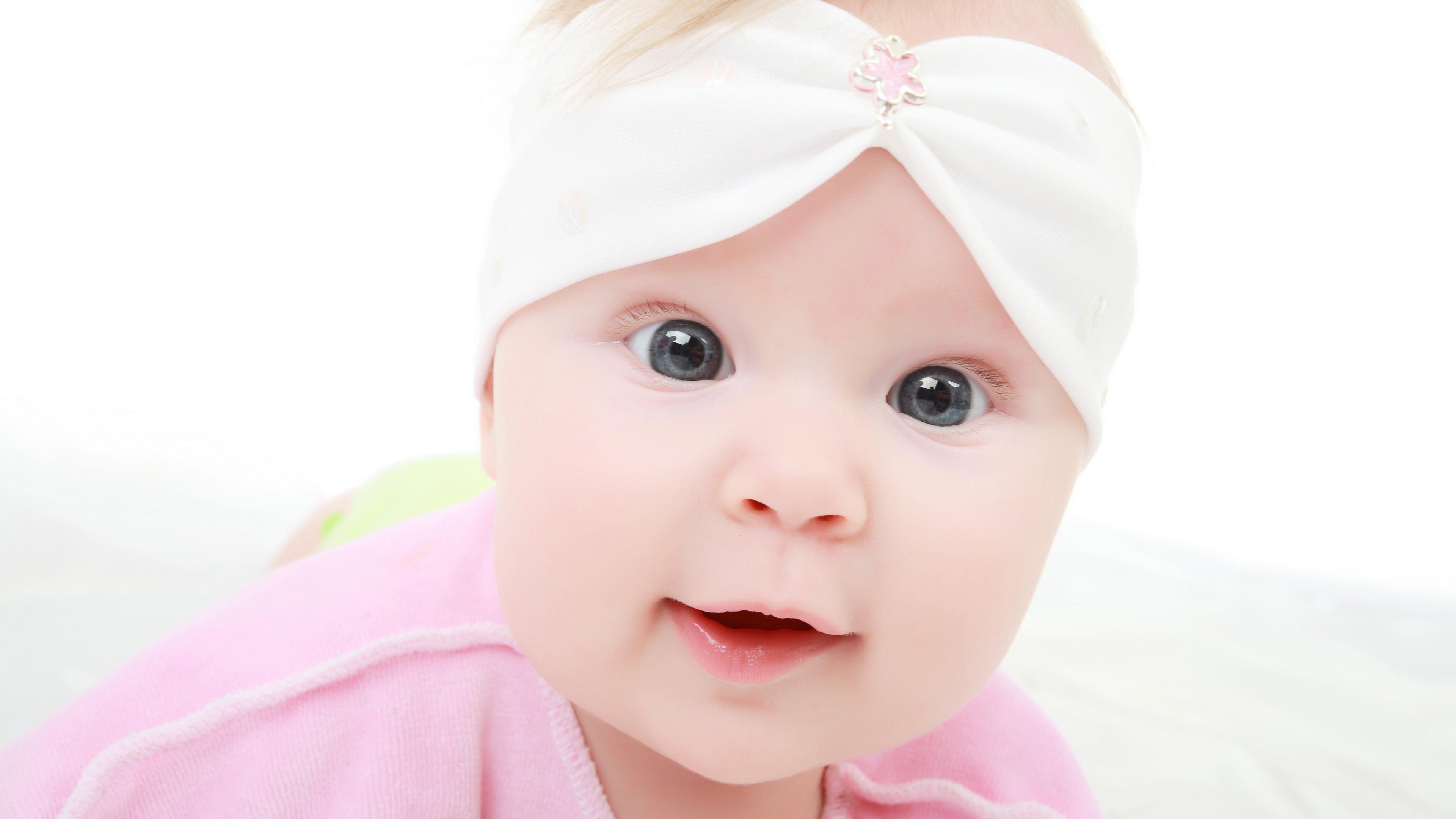 Любознательный малыш с серыми блестящими глазками и улыбкой