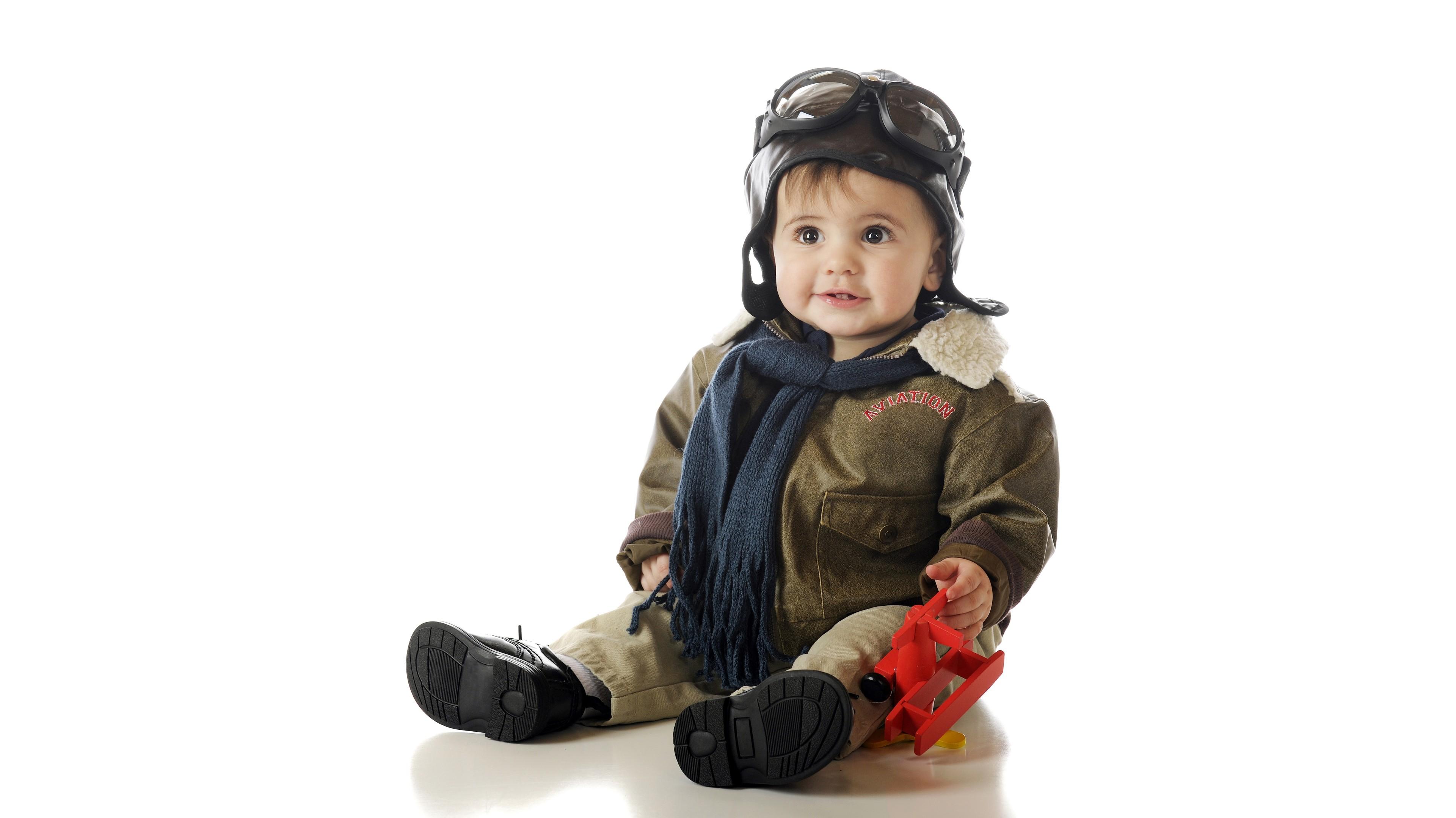 Мечтательный малыш с большими карими глазами в шлеме и очках летчика