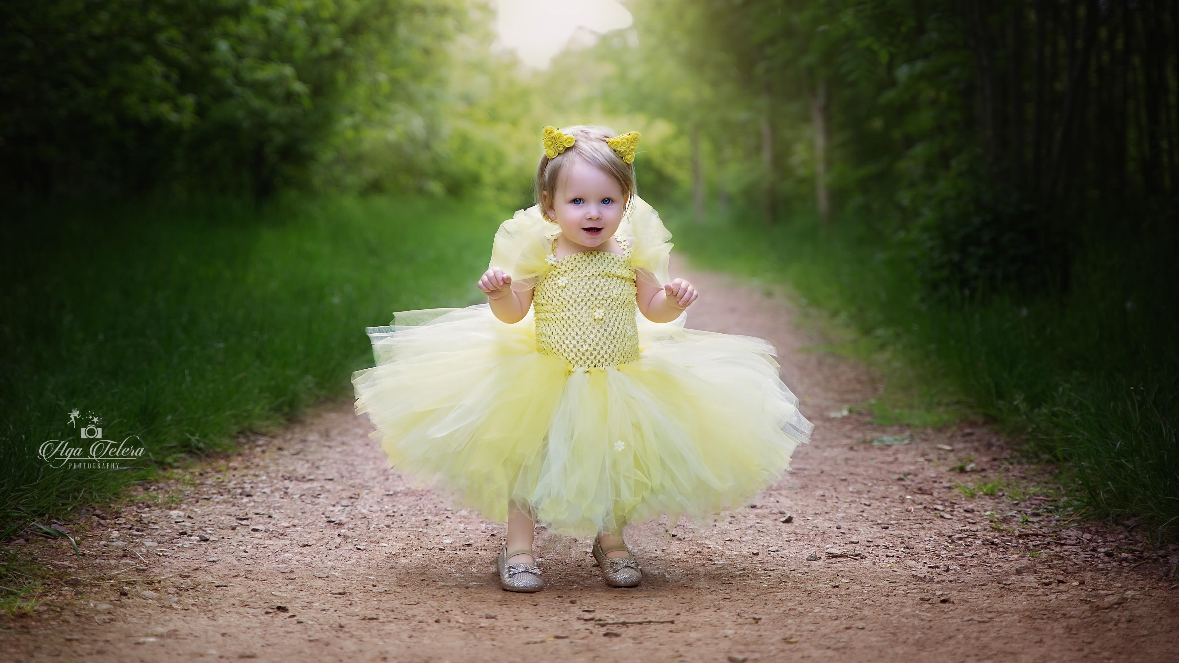Маленькая принцесса в воздушном платье с воланами на лесной тропинке