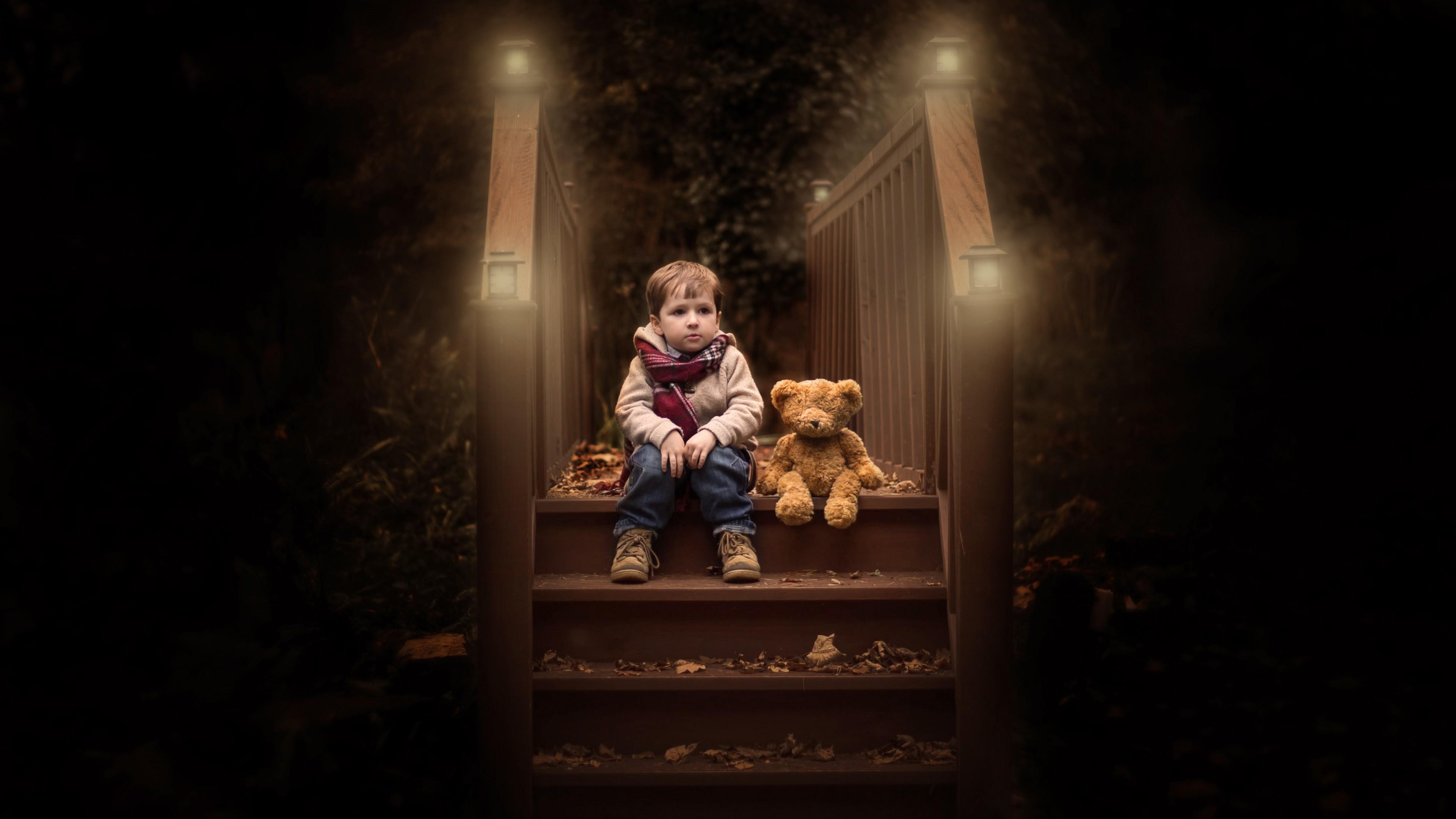 Маленький мальчик с плюшевым медведем на ступенях  сухих желтых листьев и ночных фонарей