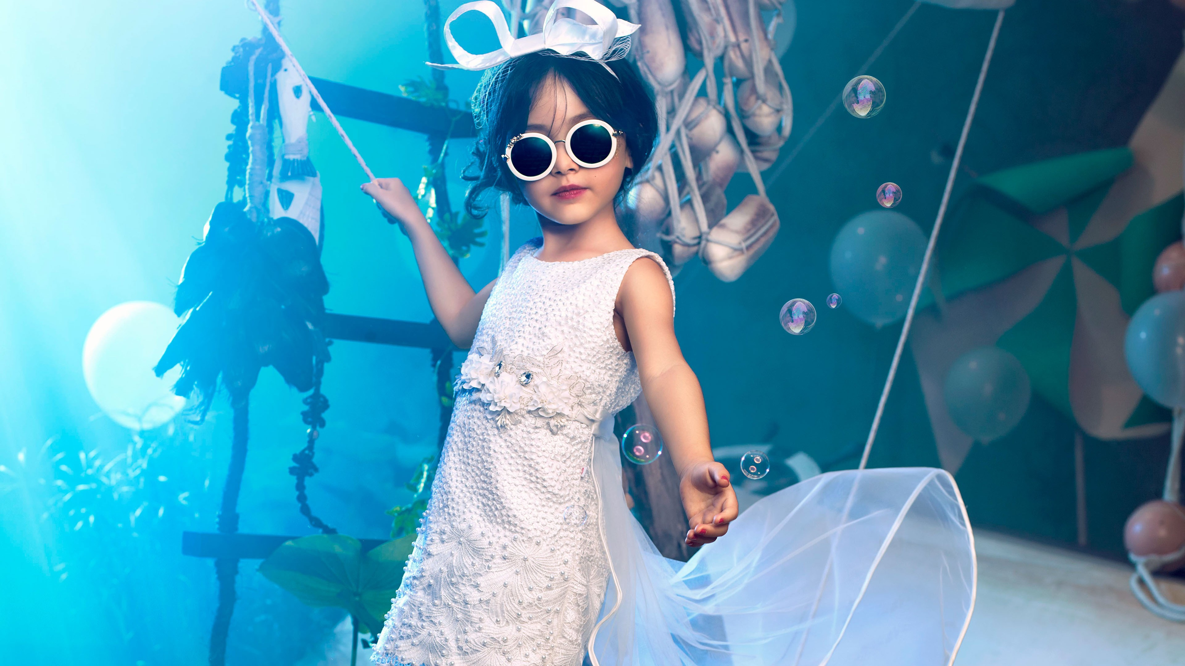 Красивая девочка в черных очках и белоснежном платье с вуалью