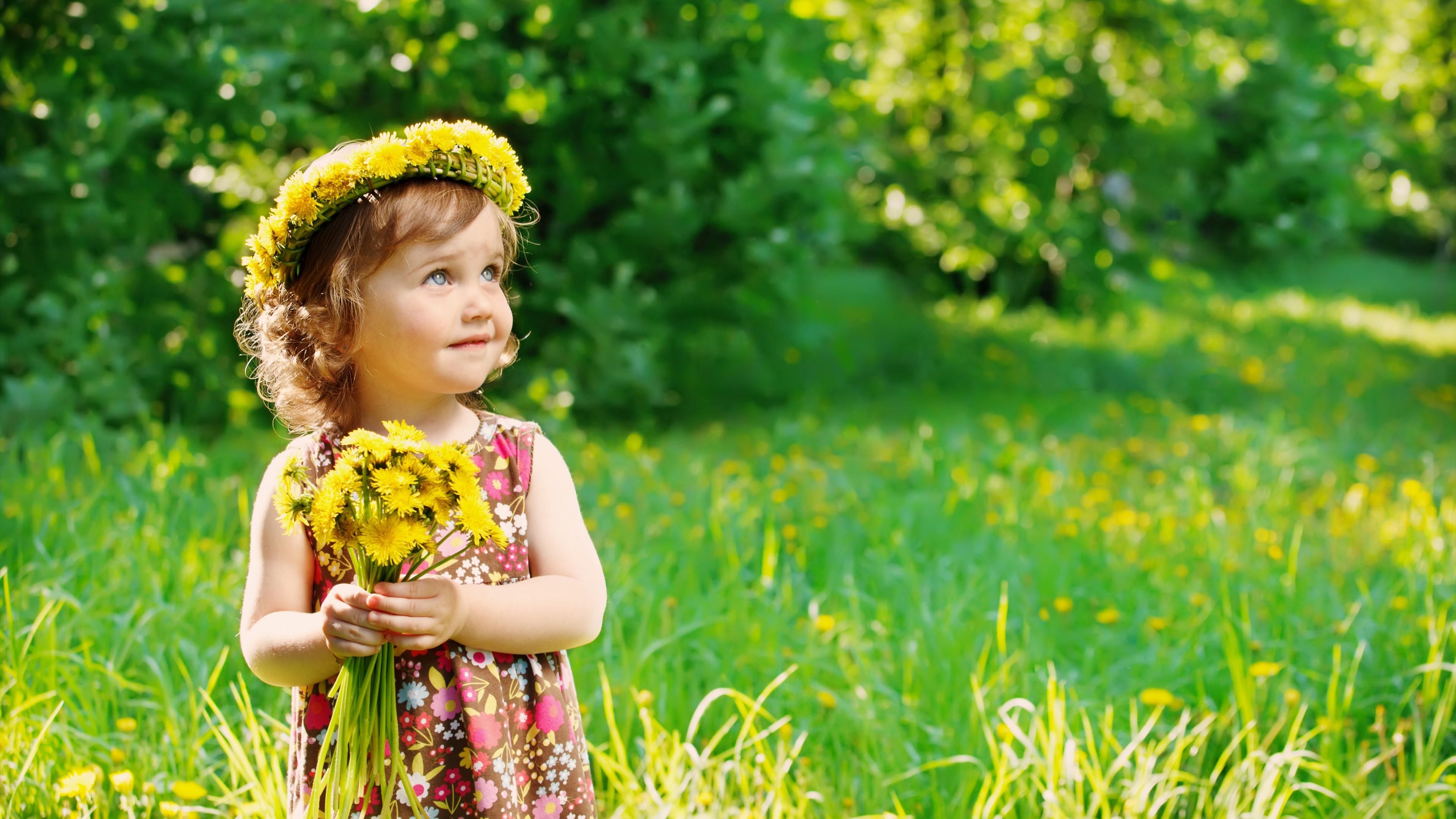 Очаровательная голубоглазая девочка с букетом желтых цветов и короной  в весеннем лесу