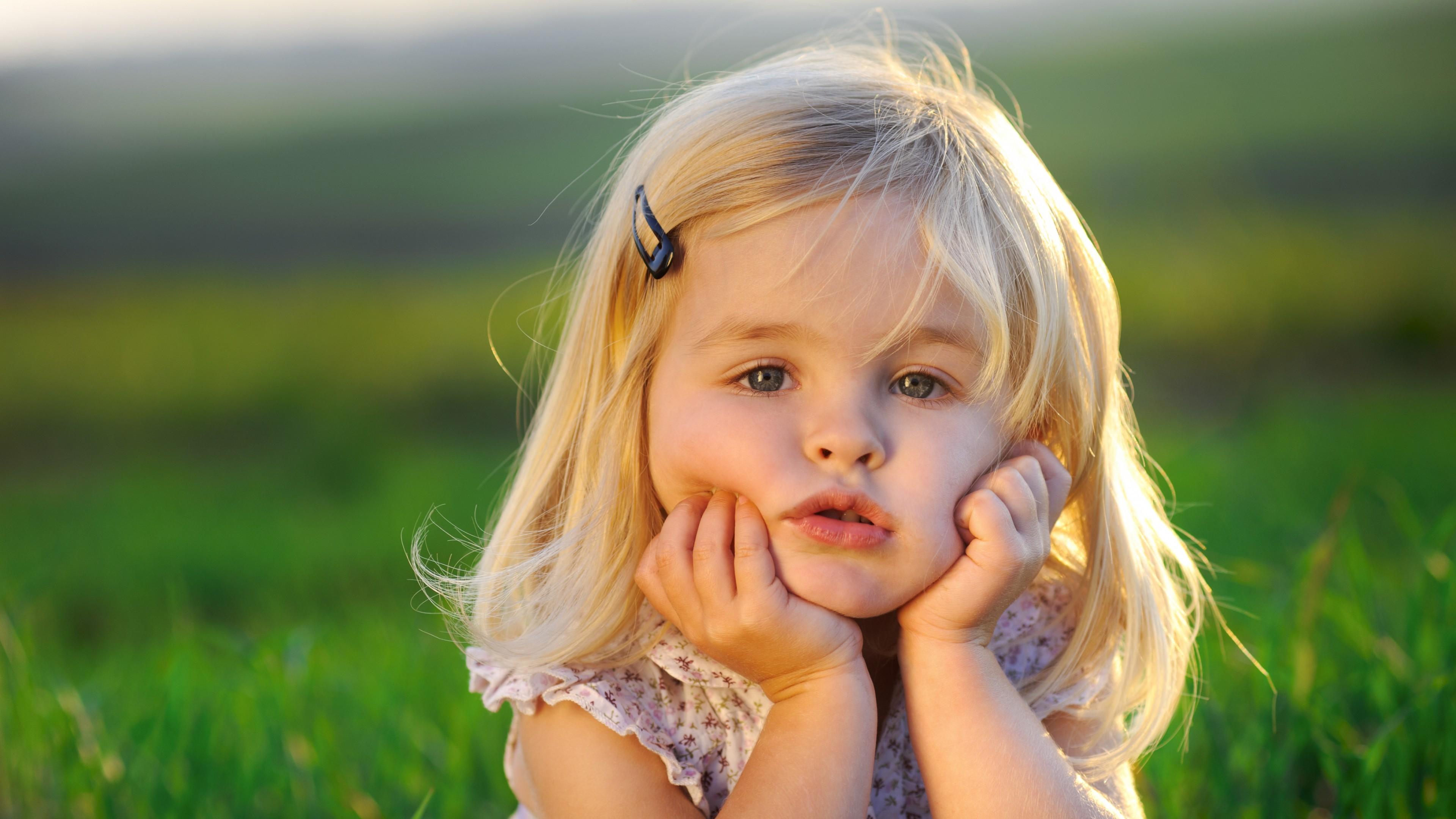 Задумчивая белокурая девочка на зеленой поляне в лучах солнца