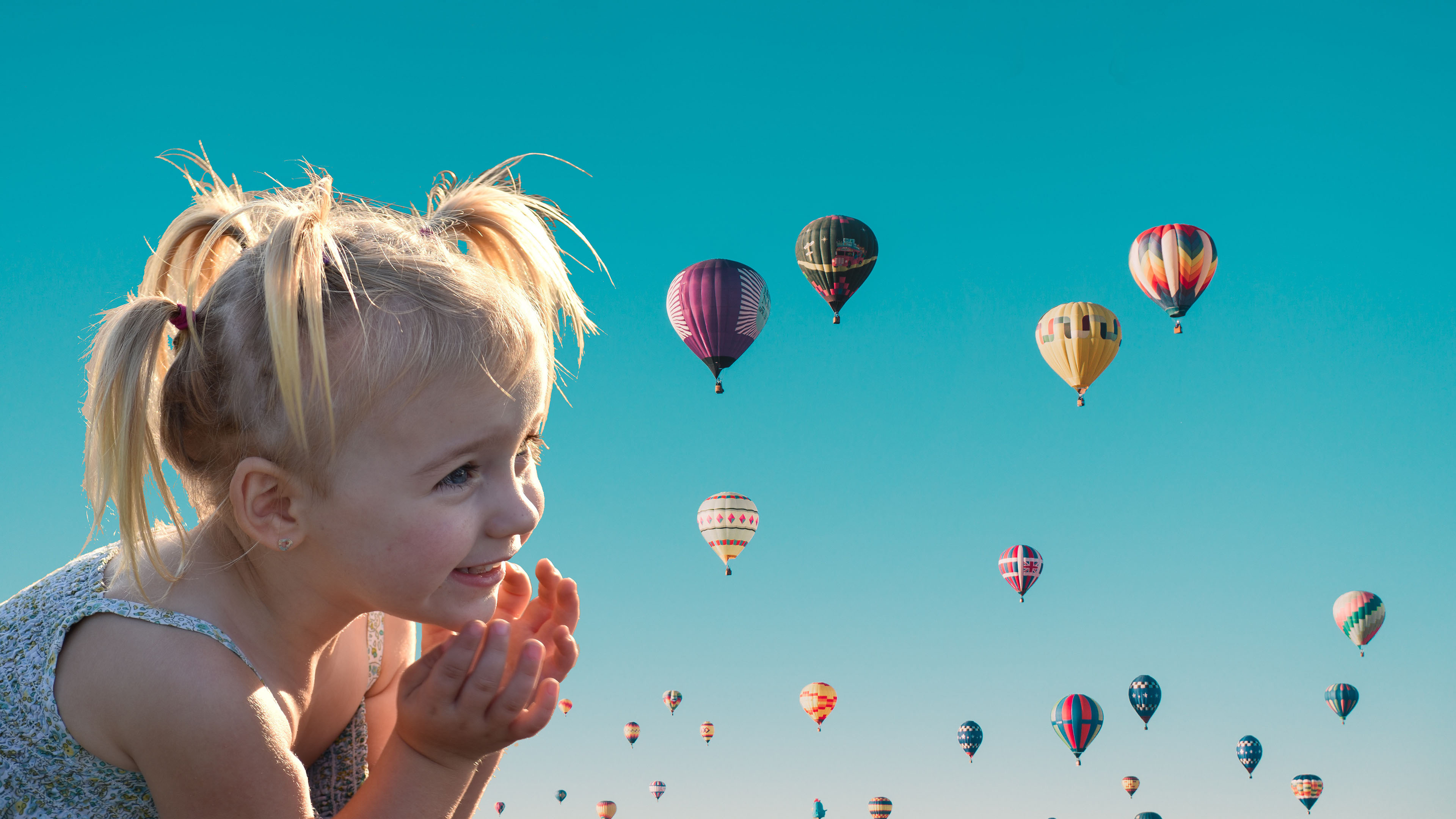 Летнее солнечное утро с воздушными разноцветными шарами и восхищение,радость белокурой девочки