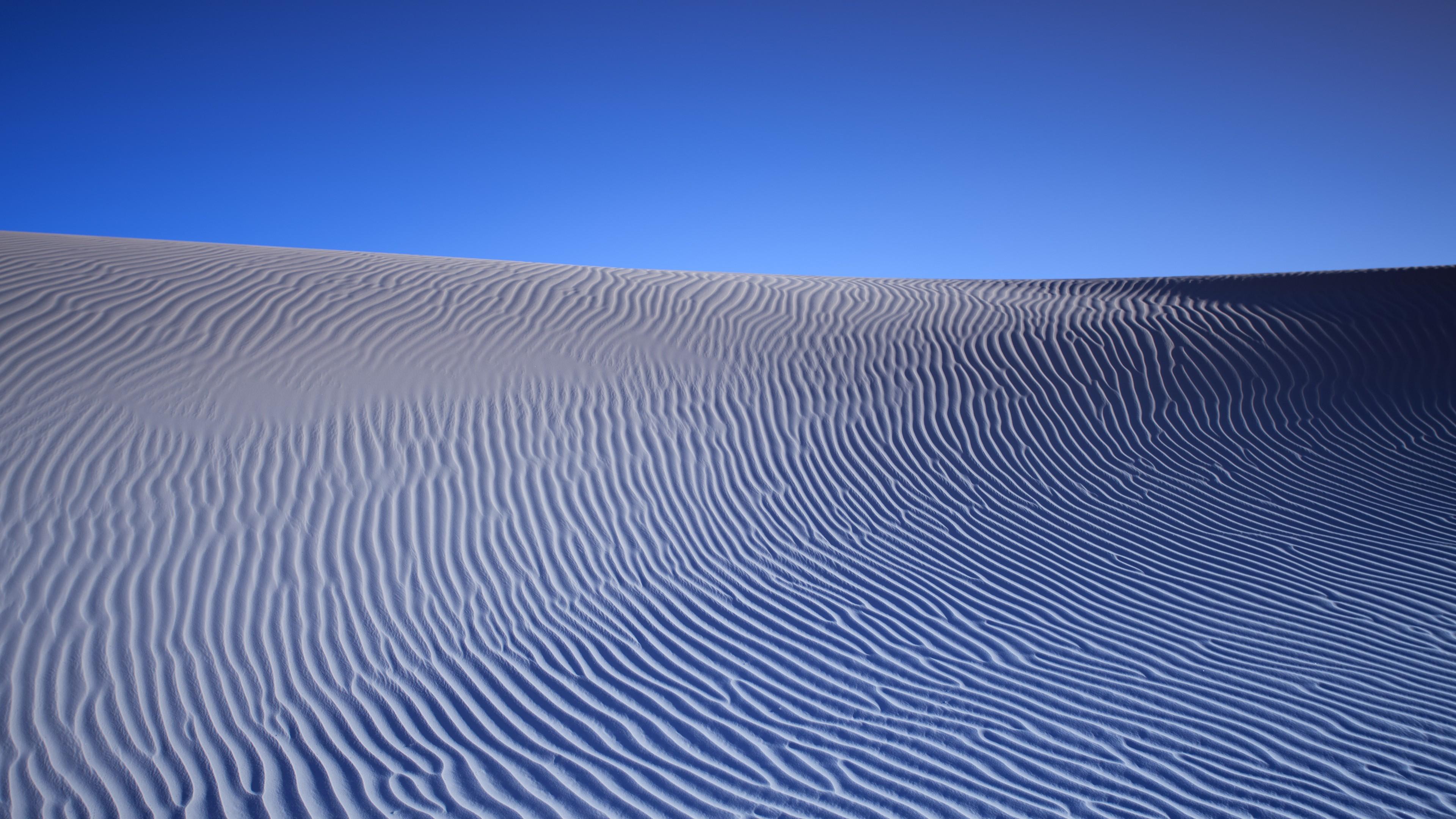 Рельефные формы пустыни в отблесках безоблачного ярко- синего неба