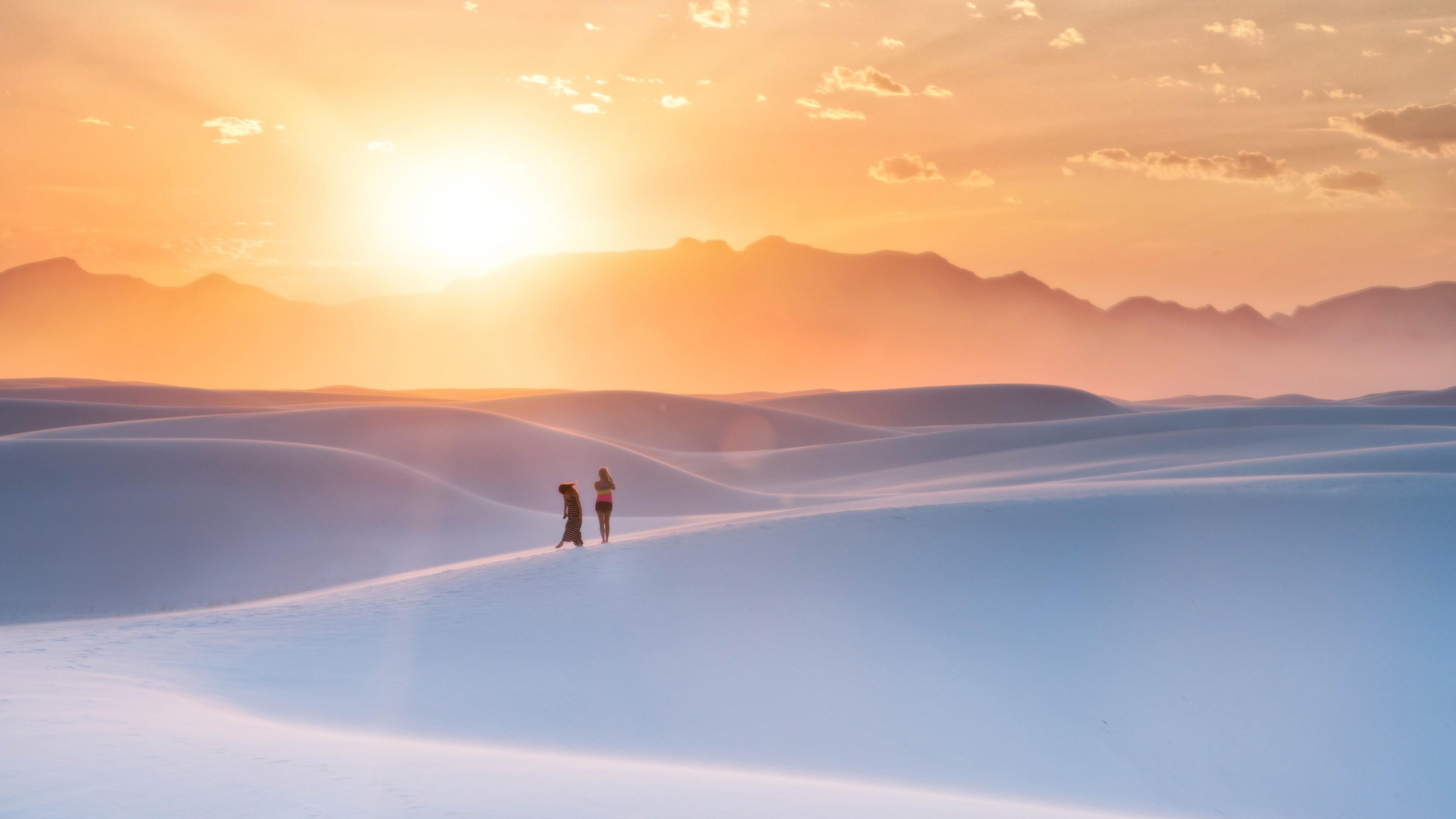 Рассветные золотые лучи солнца над белоснежными рельефными дюнами
