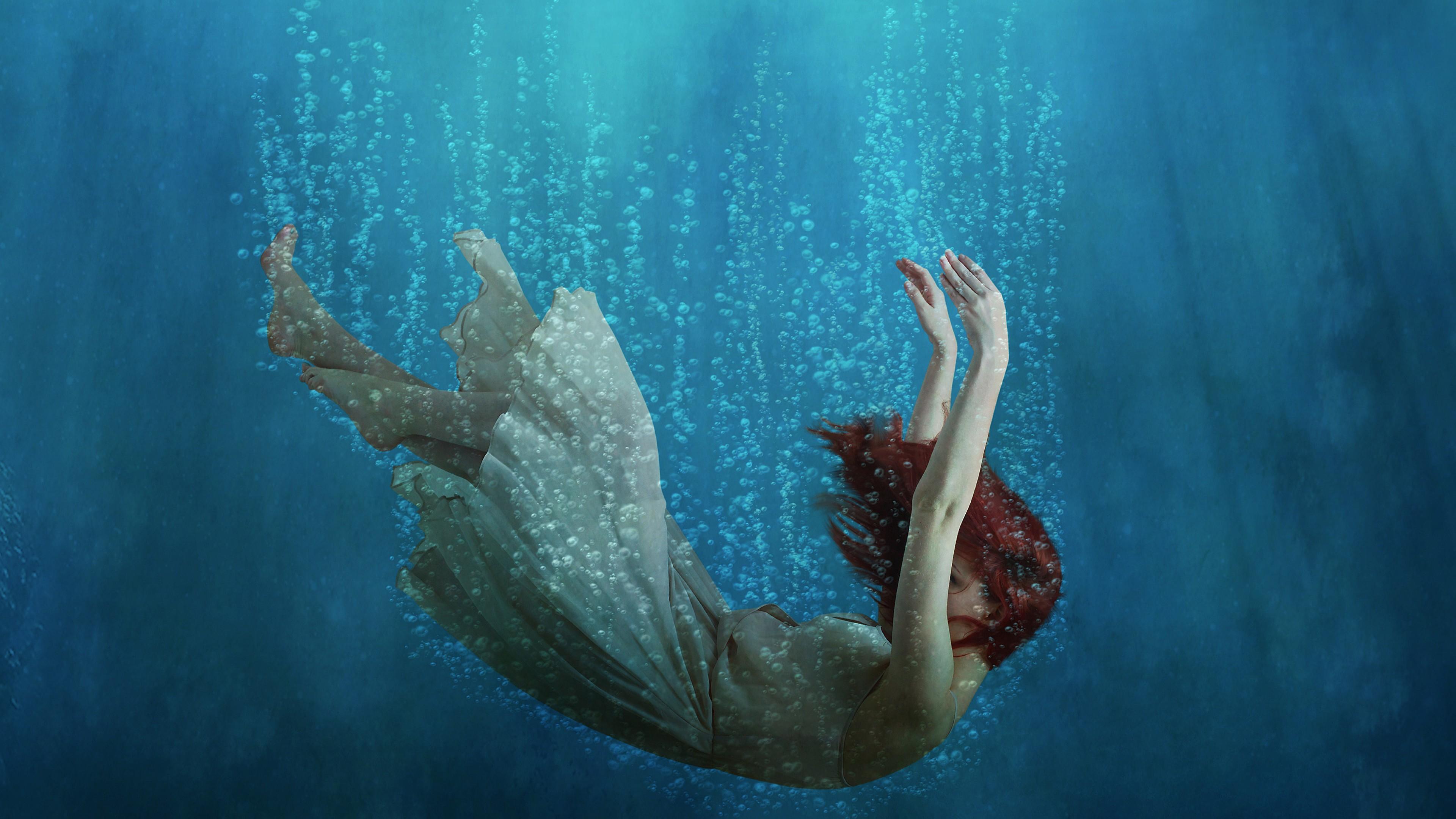 Падающая девочка в синих водах океана с  белыми струйками воздуха