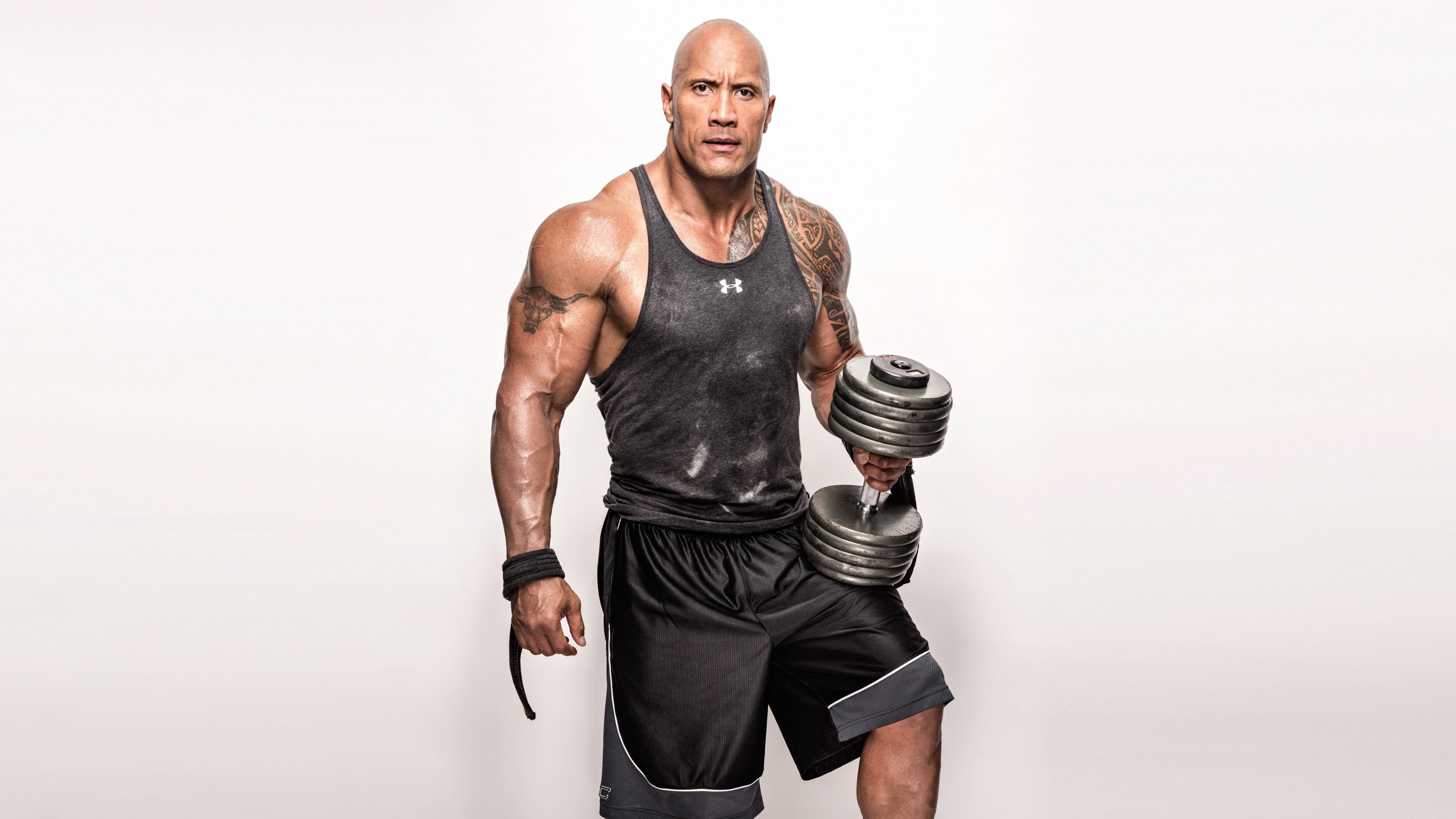 Спортивного телосложения борец с тату на плече и с гантелью в руке