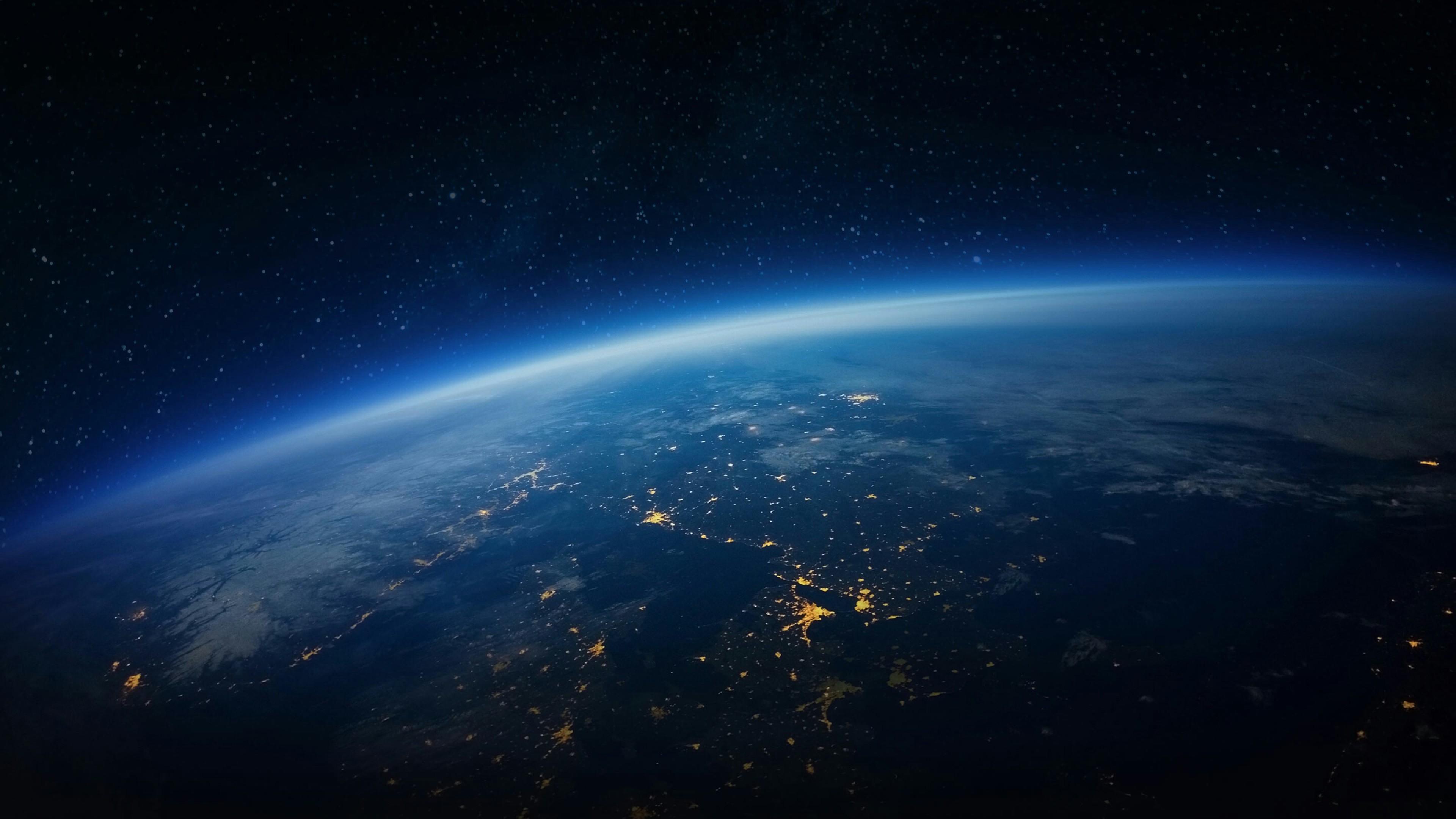 Голубая планета Земля в отблесках и свечении звездной Вселенной