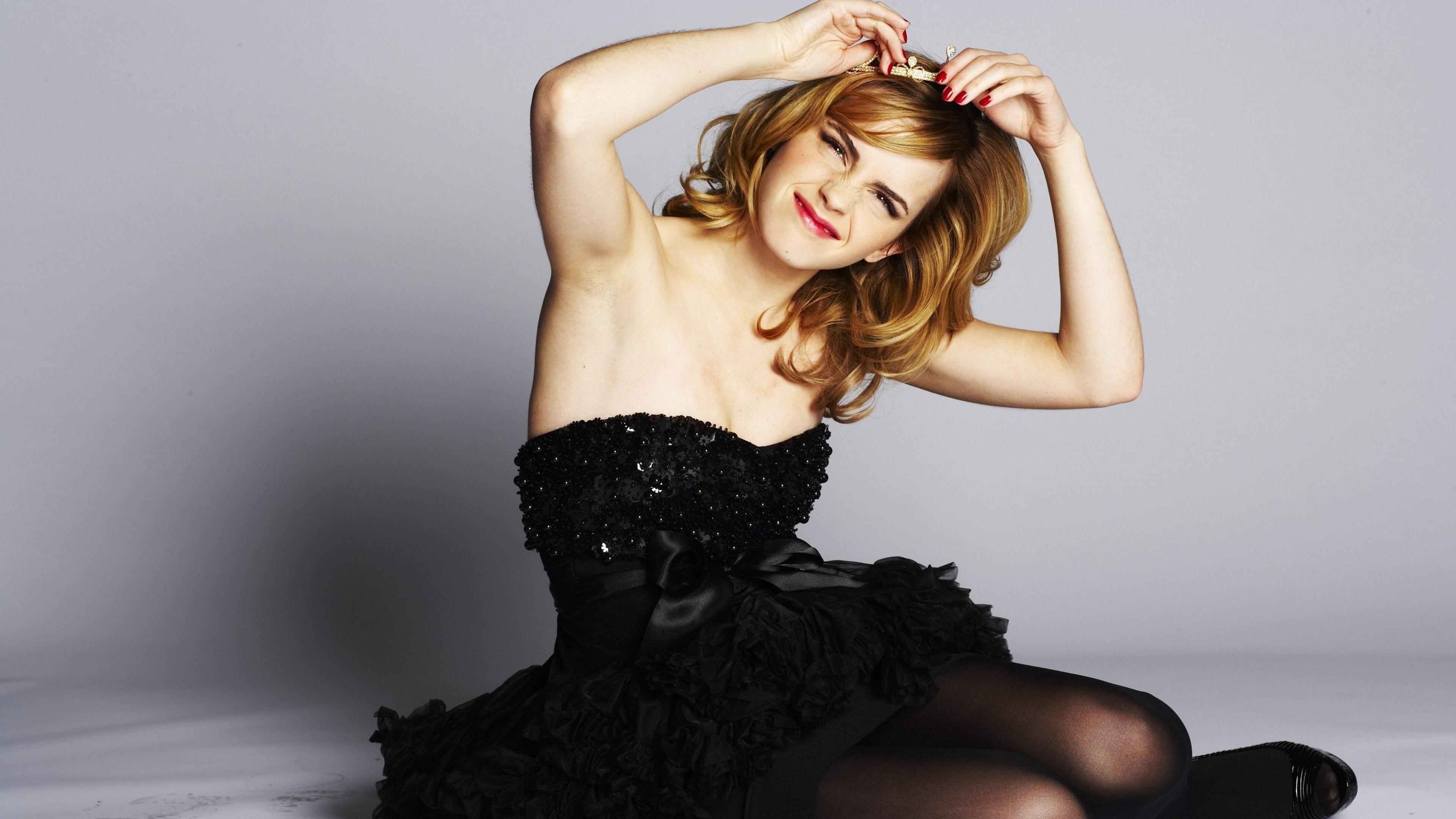 Рыжеволосая девушка с прищуренным взглядом в черном платье с открытым декольте