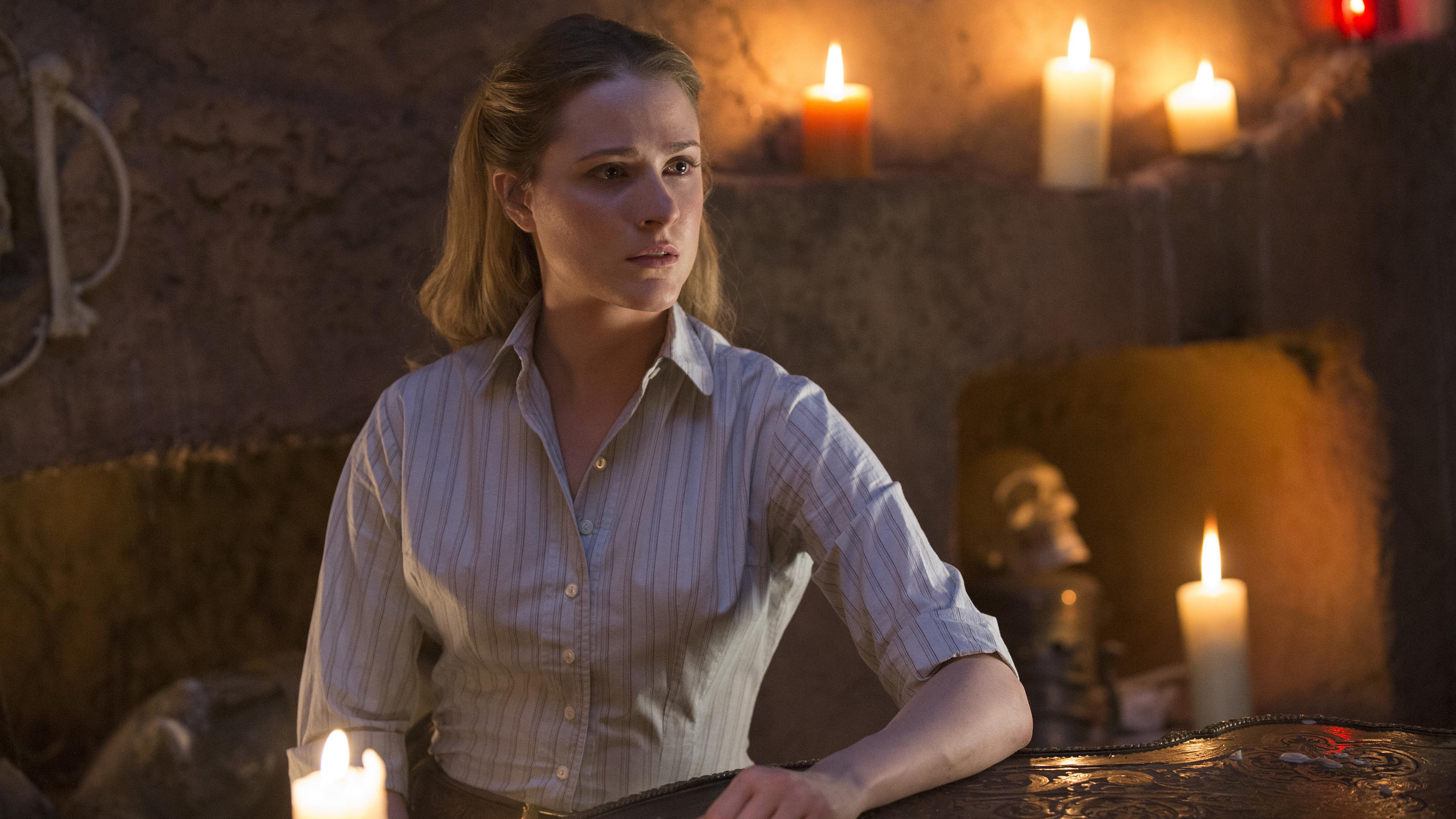 Светловолосая девушка в заброшенном доме горящих свечей