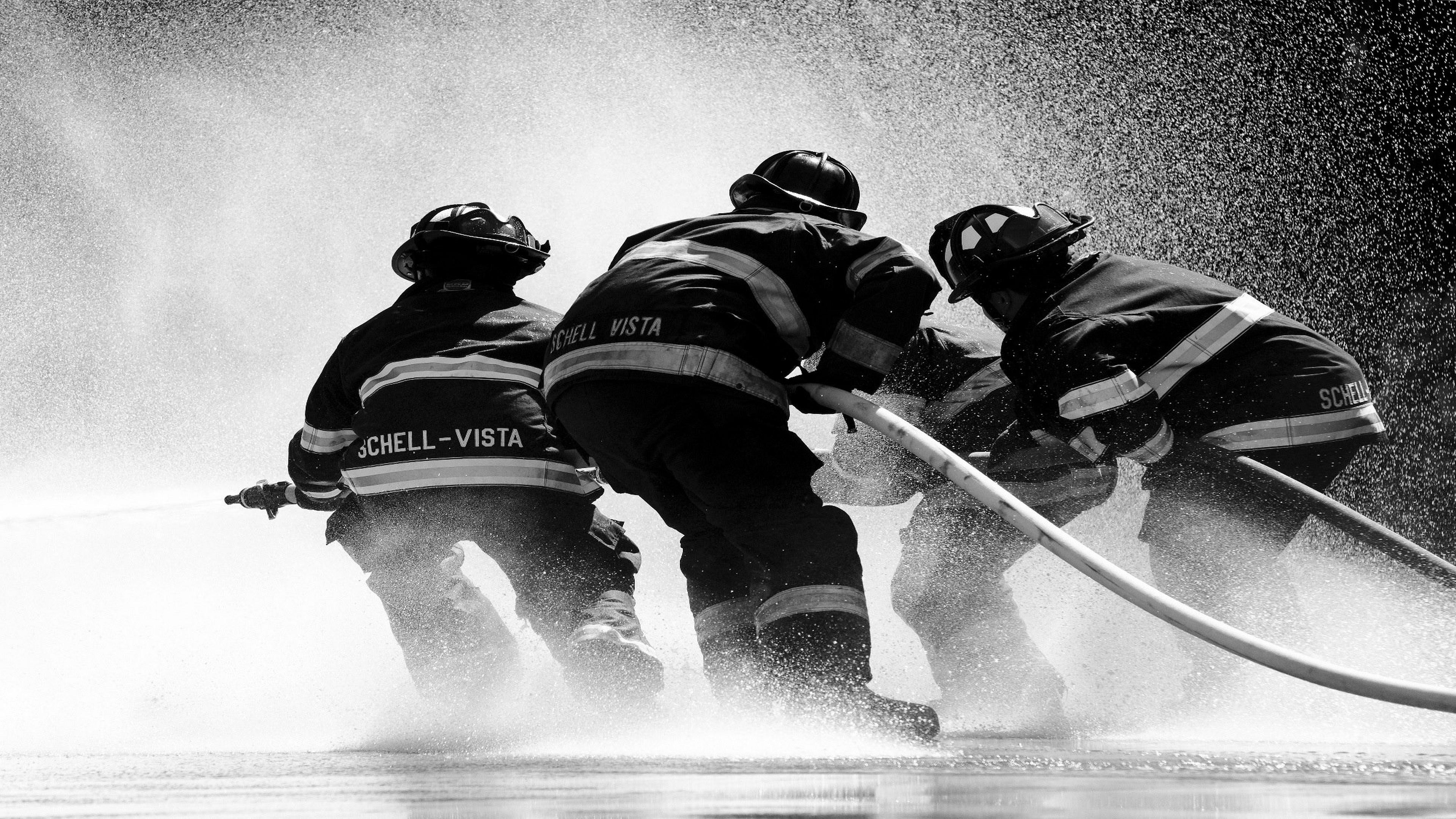 Спасатели в касках и спецодежде с помощью насосов с пеной тушат пожар