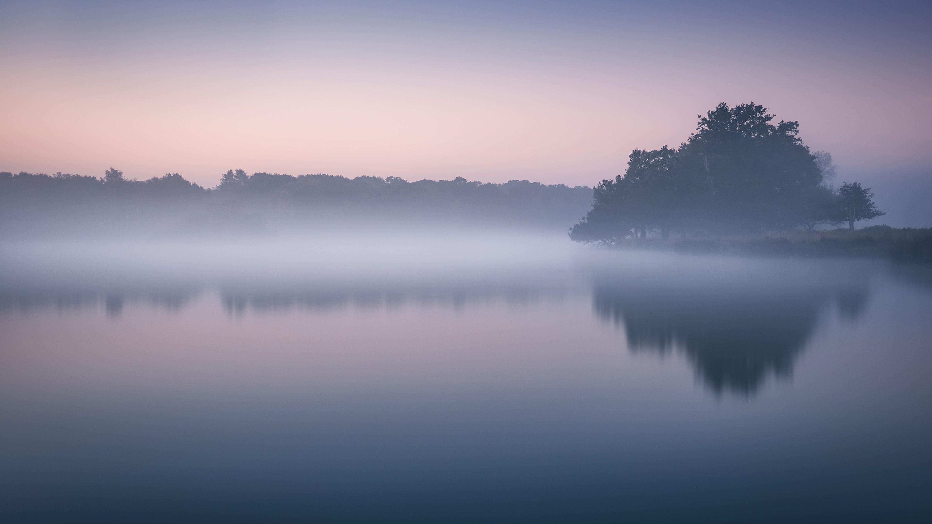 Голубая рассветная дымка тумана над речной гладью
