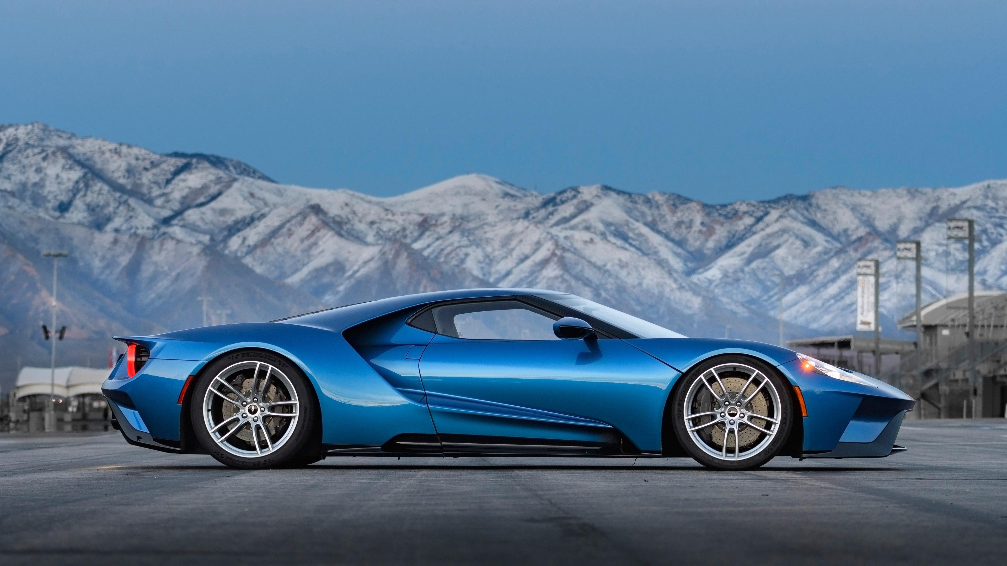 Синий спортивный дизайнерский автомобиль на фоне снежных вершин