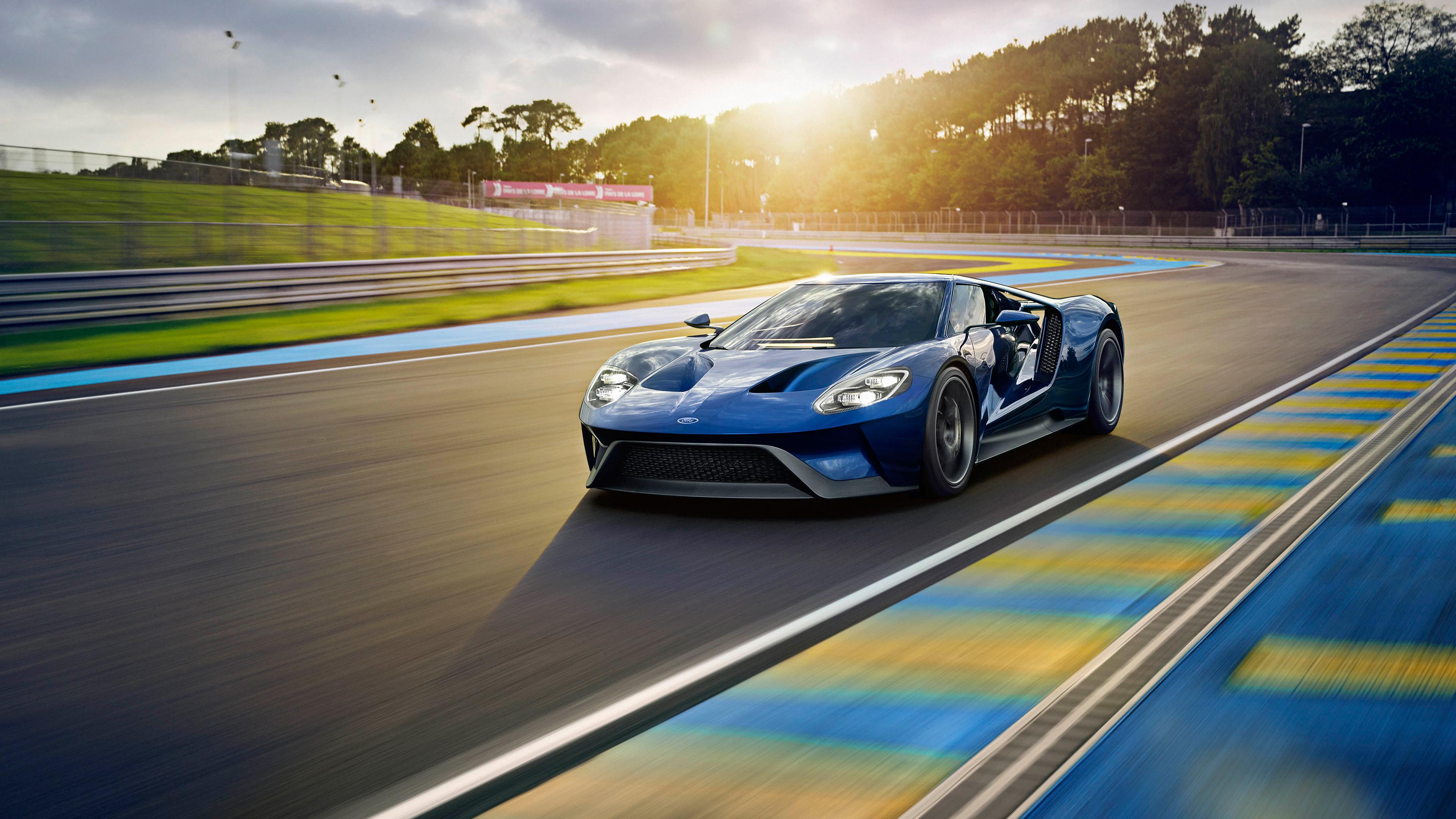 Блестящий спортивный мощный автомобиль мчится  по трассе с разделительными полосами