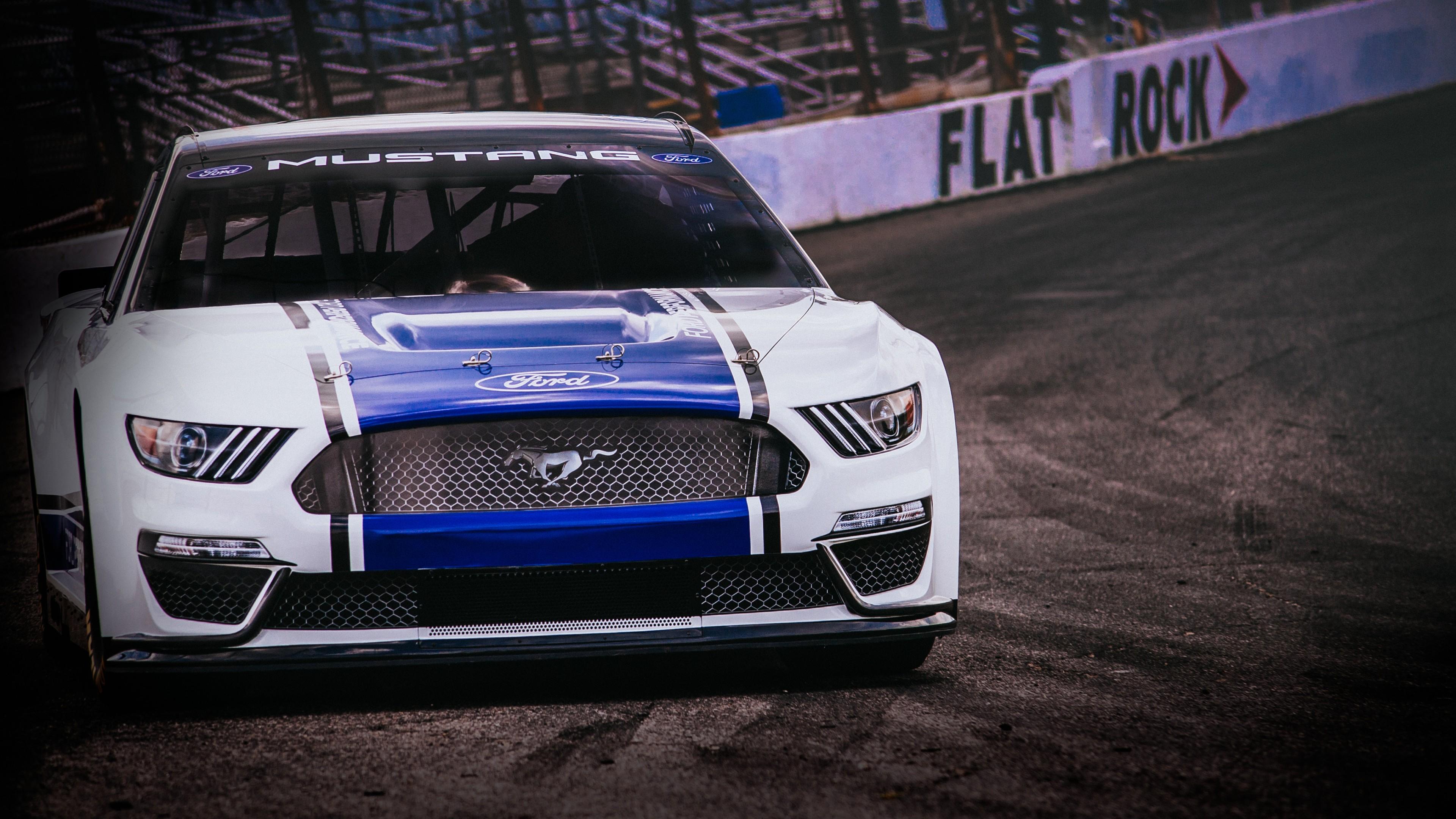 Бело-синий спортивный автомобиль с эмблемой Мустанга